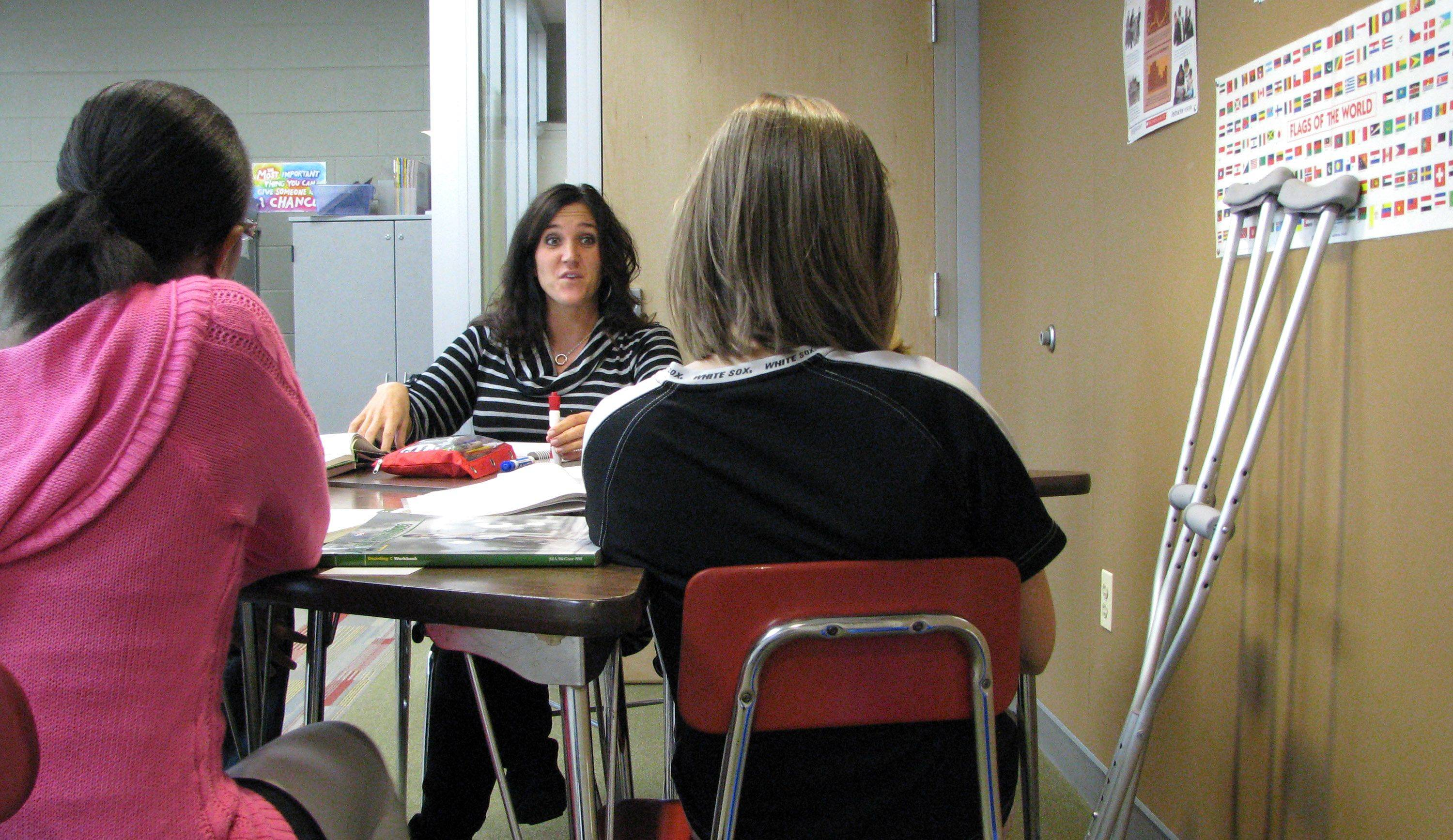 Naperville Central High School special education teacher Natalie Billings works on reading Friday with her students.
