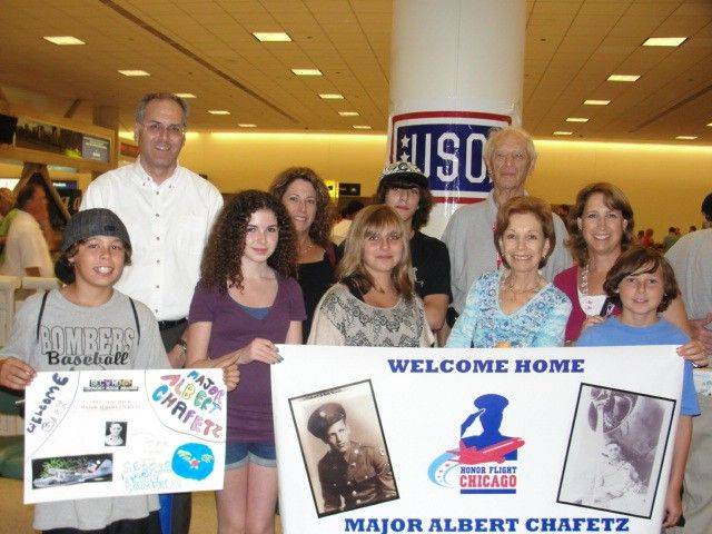 Sam Herzog, far right, and his family welcome his grandfather back from an Honor Flight at Midway Airport.