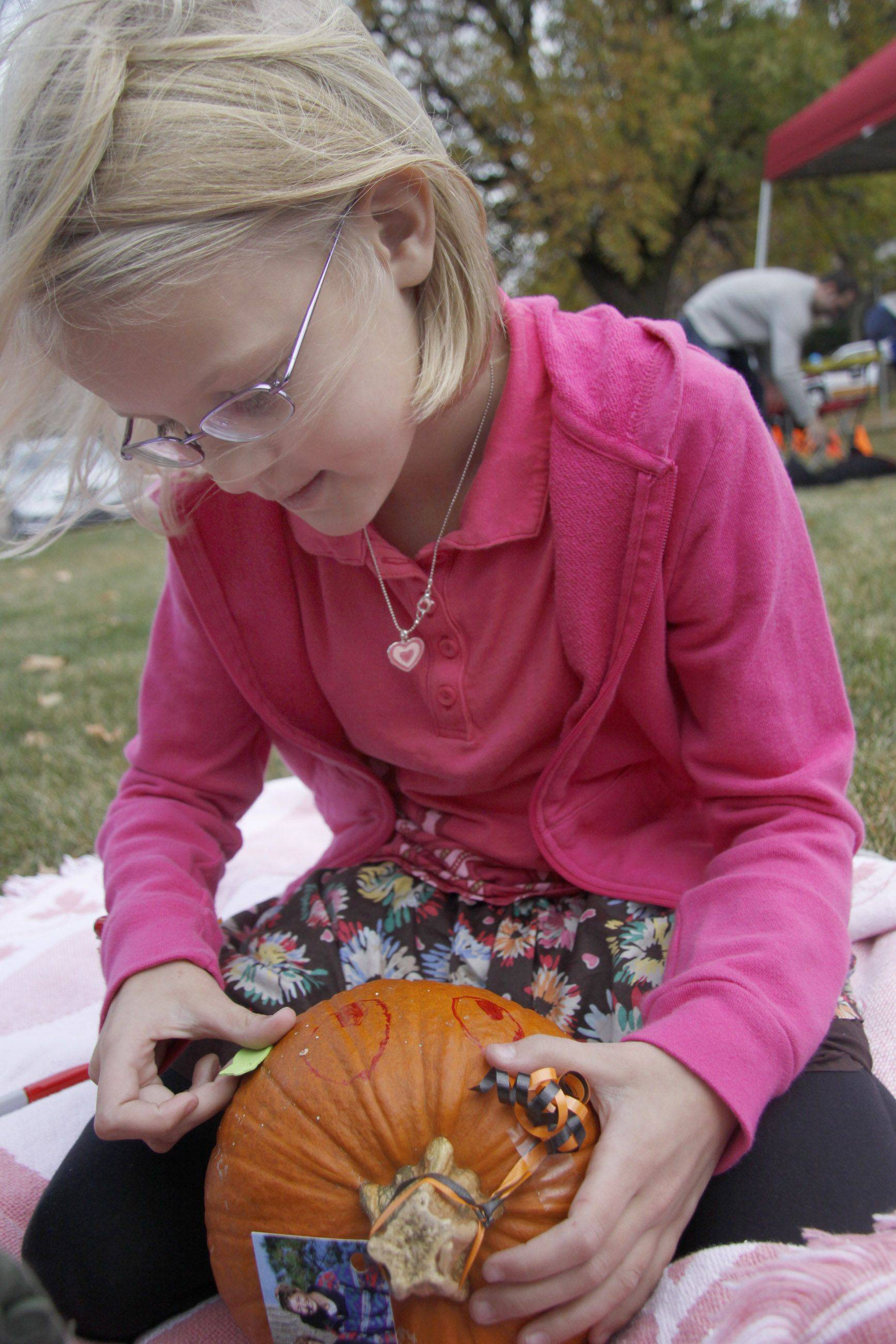 Sydney Alpers, 8, of Wheaton decorates the free pumpkin at Make a Difference Day in Wheaton.