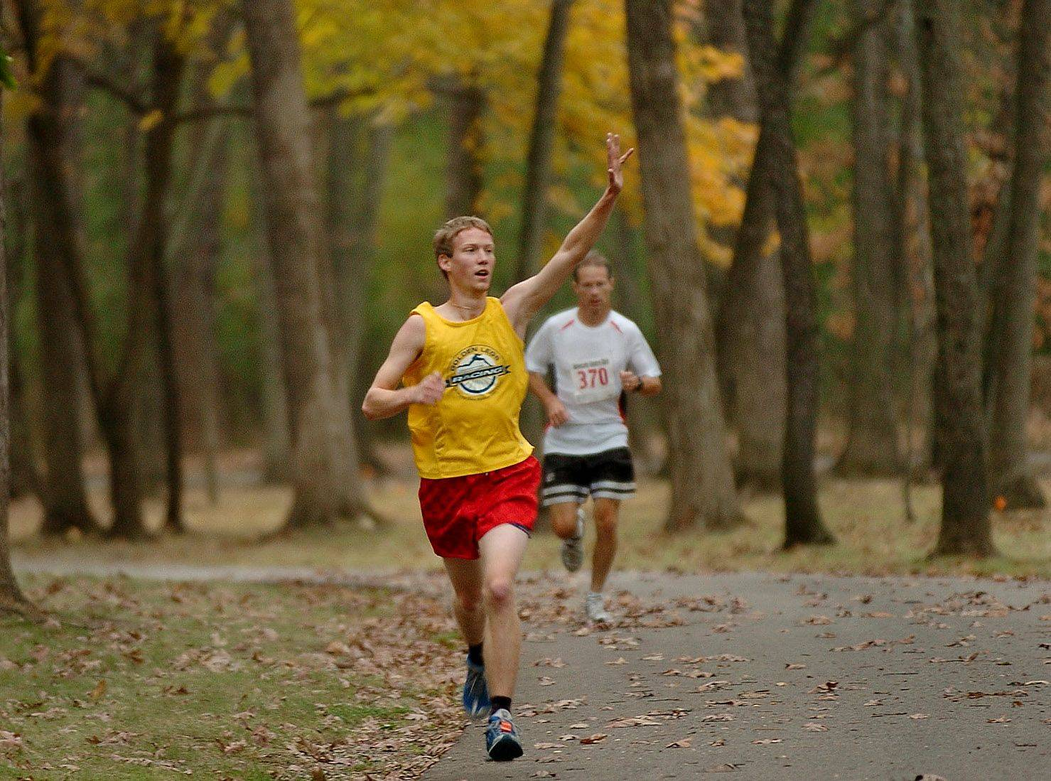 Tony Volpentesta of Mundelein signals to a friend as he runs through the woods during the first-ever Advocate Condell Centre Club Pink Ribbon run at St. Mary of the Lake Seminary in Mundelein. Tony eventually finished second in the 5k race.