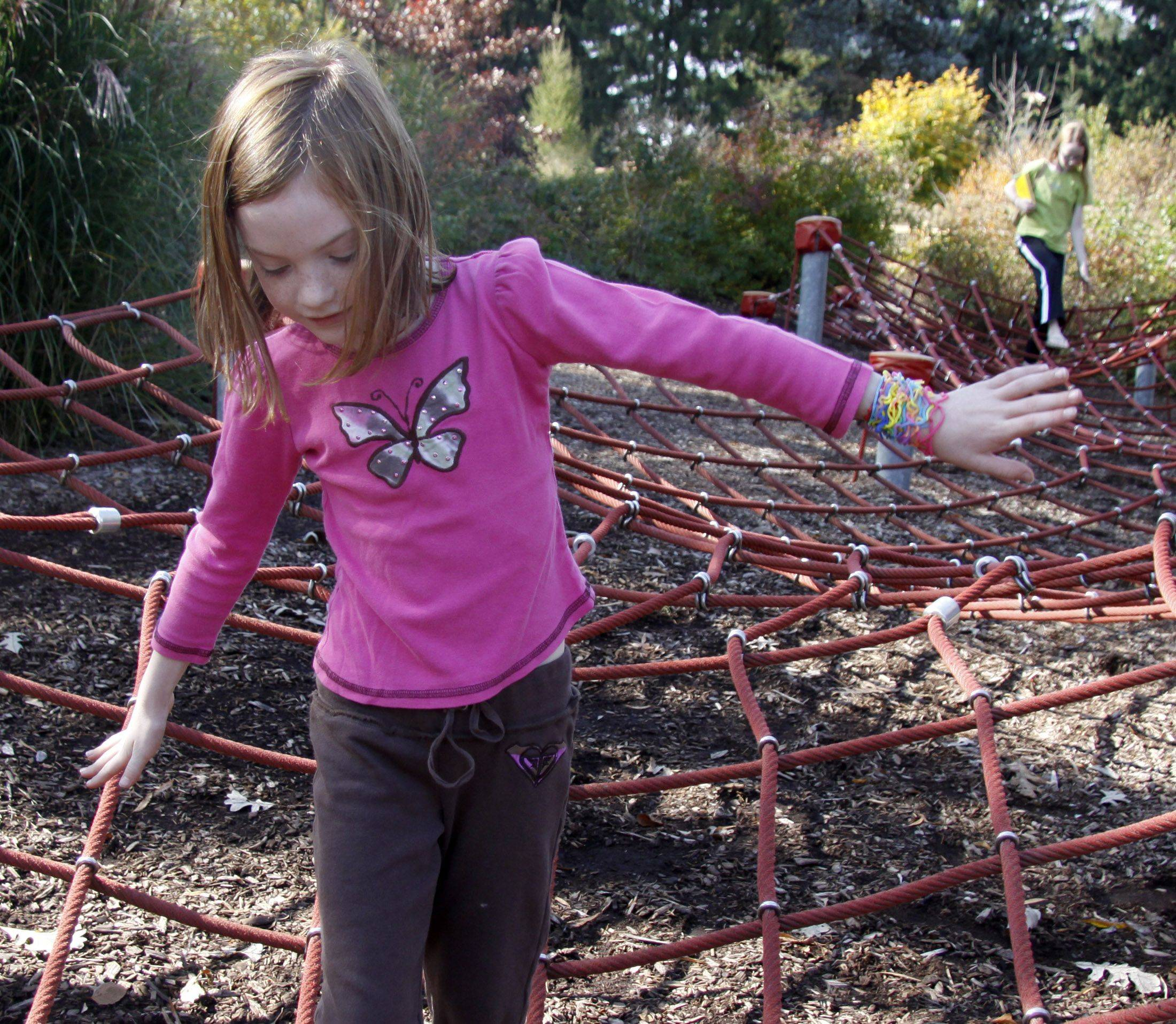 Maeve Seyer, 6, of LaGrange Park walks through a spider web in the kids area of the Morton Arboretum Sunday. The Arboretum held its Fall Festival which had a variety of activities and events for children to partake in.