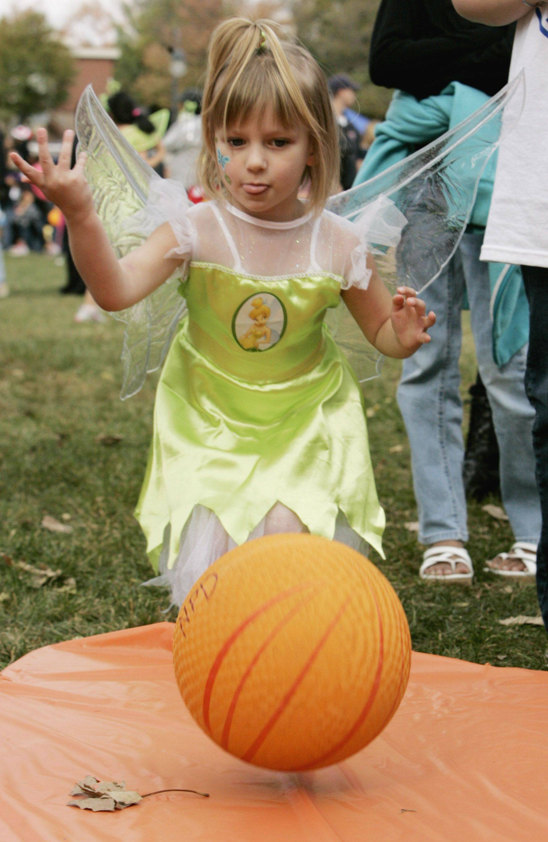 Ava Gusel,4, of Downers Grove plays a Halloween bowling game Sunday as part of the Halloween Happening at the Grand Pavilion along Naperville's Riverwalk.