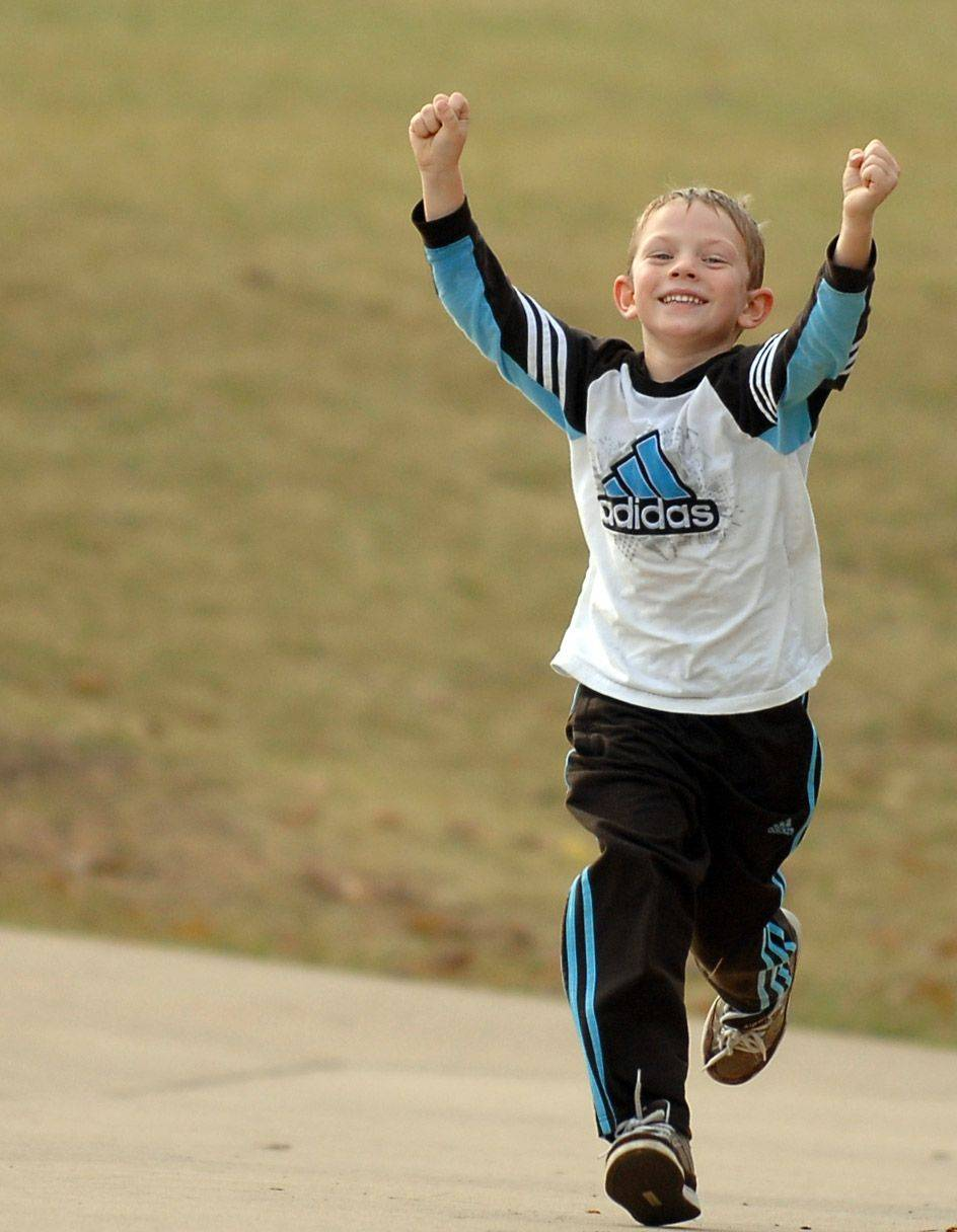 First-grader Nicky O'Keeff throws up his arms as he approaches the finish line during Heartland Elementary School's annual one-mile Run from the Heart in Geneva Monday. The event is part of Red Ribbon Week.