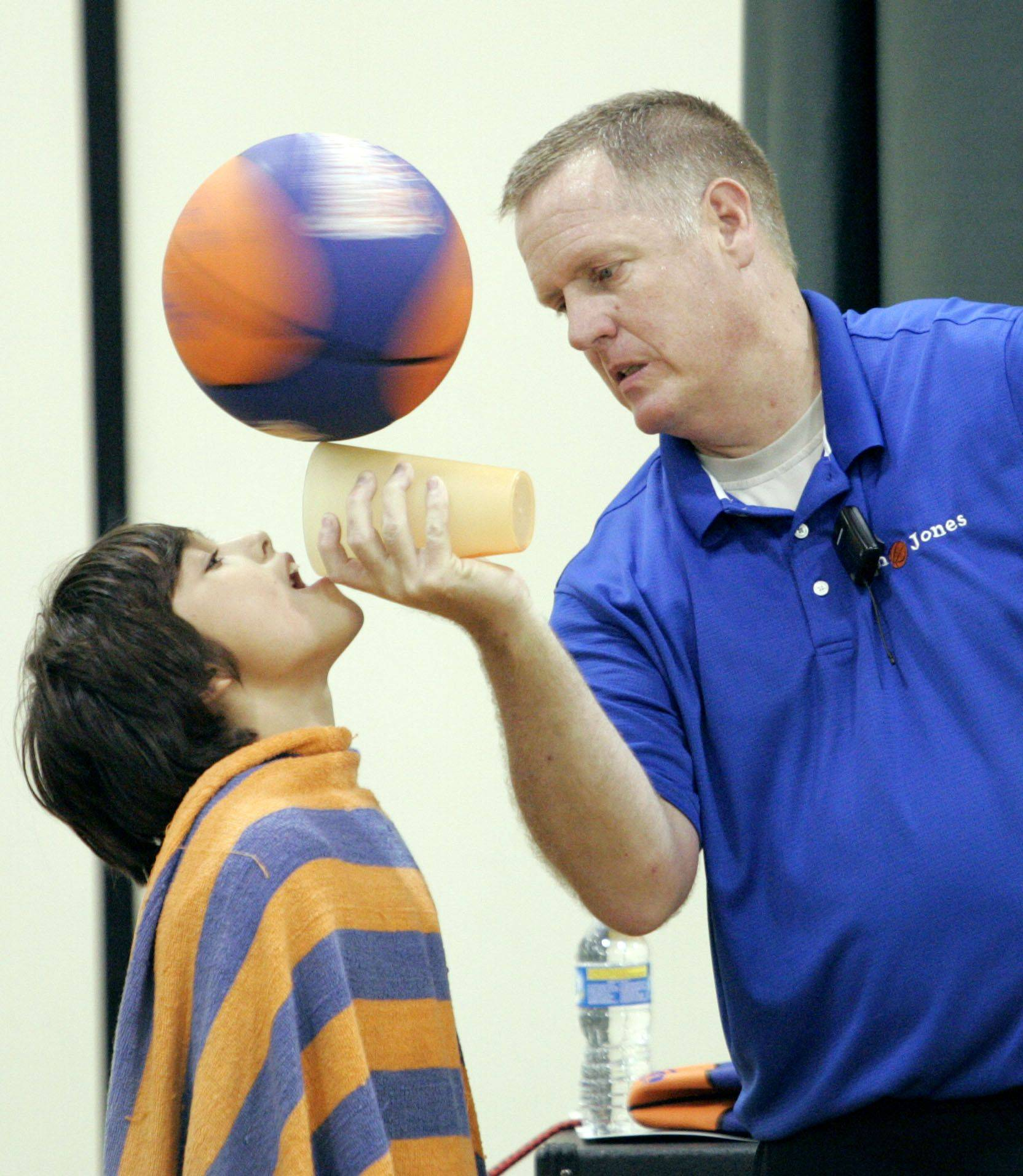 "Jim ""Basketball"" Jones spins a basketball on a cup while pouring a drink into fifth grader Drew Keirn's mouth during an assembly at Butterfield School in Libertyville Monday. Jones' message focuses on character building, making good choices and believing in yourself."
