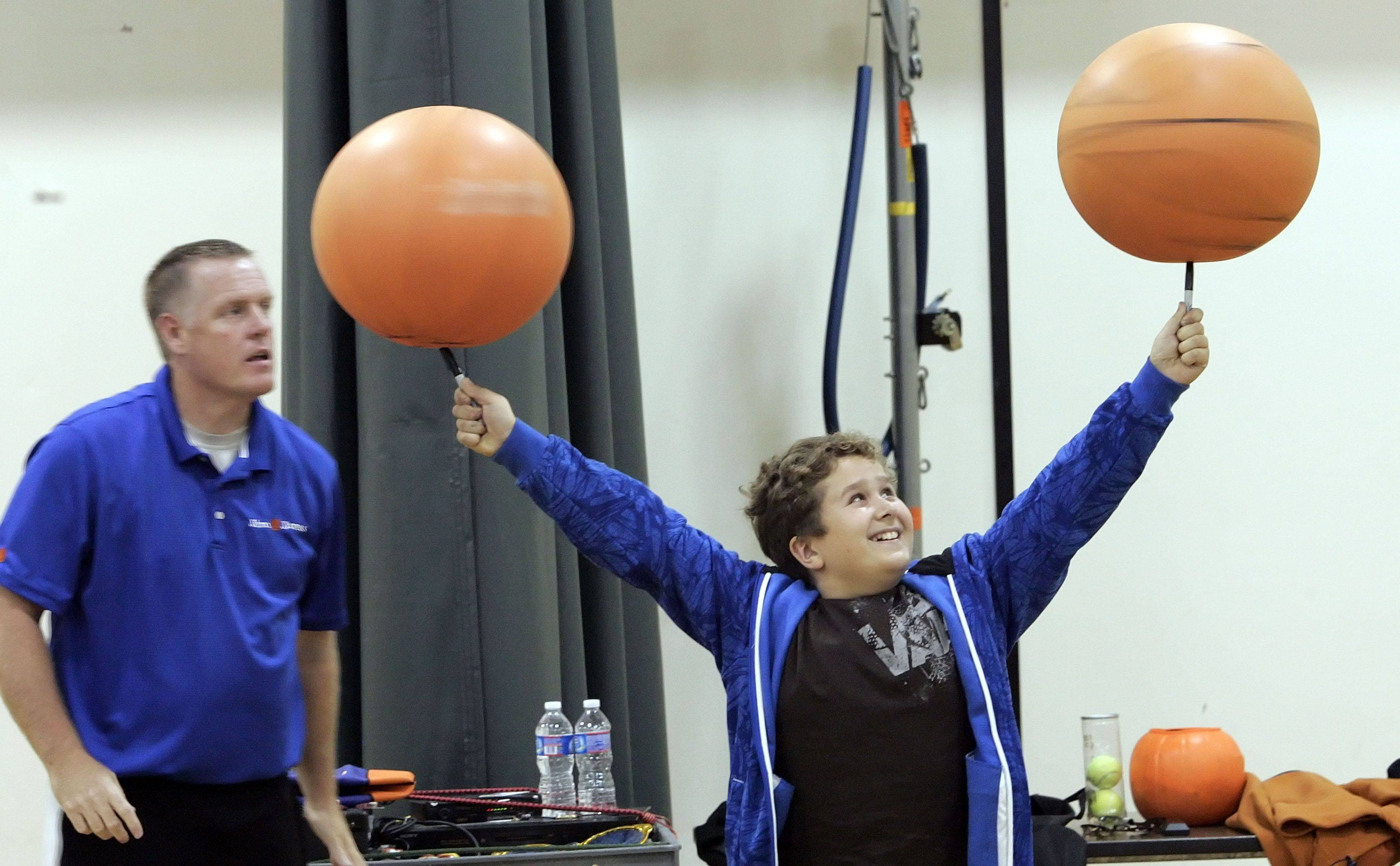 "Jim ""Basketball"" Jones helps third grader David Serrichia to spin two basketballs during an assembly at Butterfield School in Libertyville Monday."