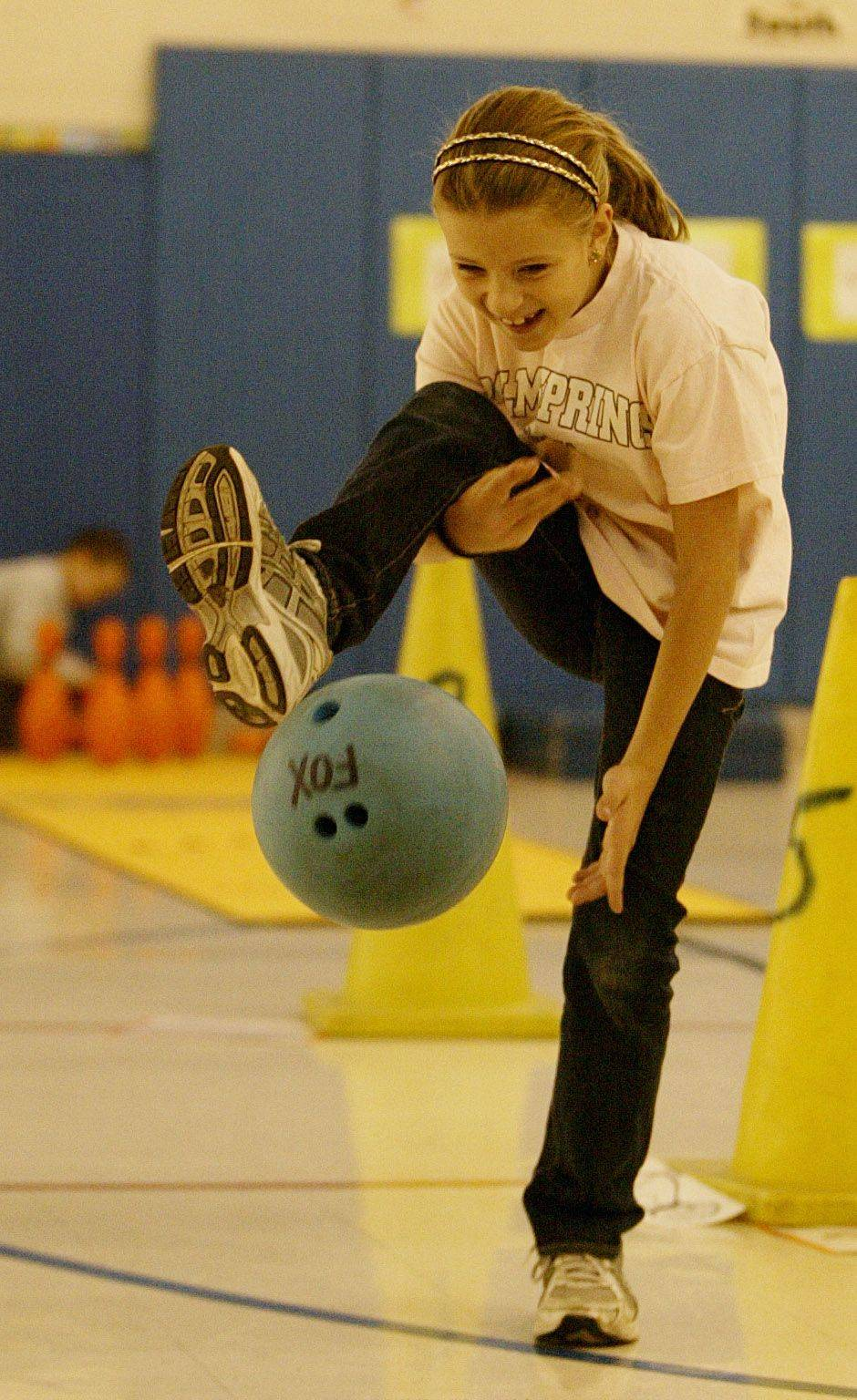 Margaret Carlisle, a third grader at Longfellow Elementary school in Wheaton bowls under one leg during physical education class in Wheaton.