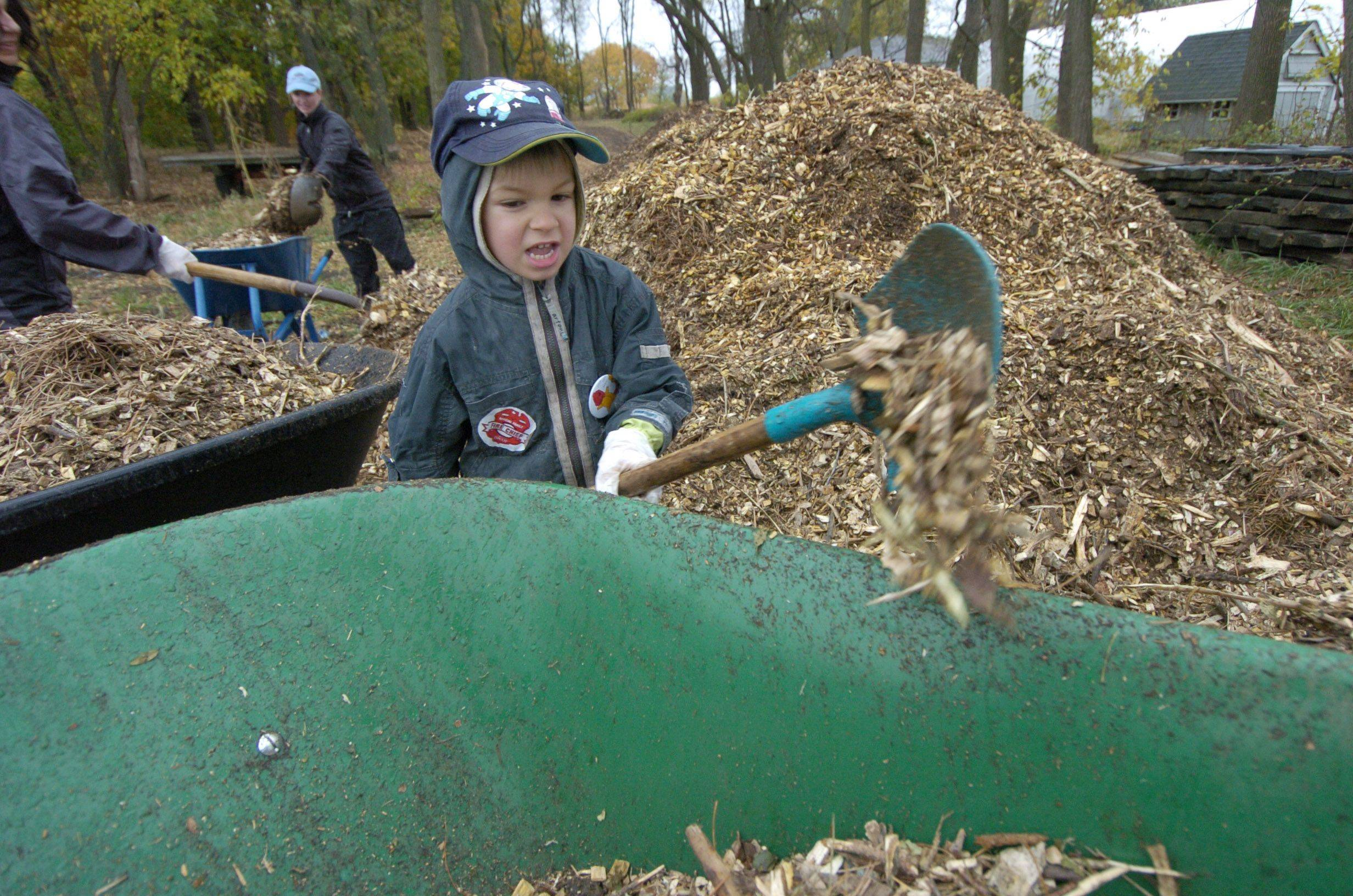 Mikey Todorova, 5, of Buffalo Grove shovels mulch during Saturday's Make a Difference Day event at Prairie Crossing Learning Farm in Grayslake.