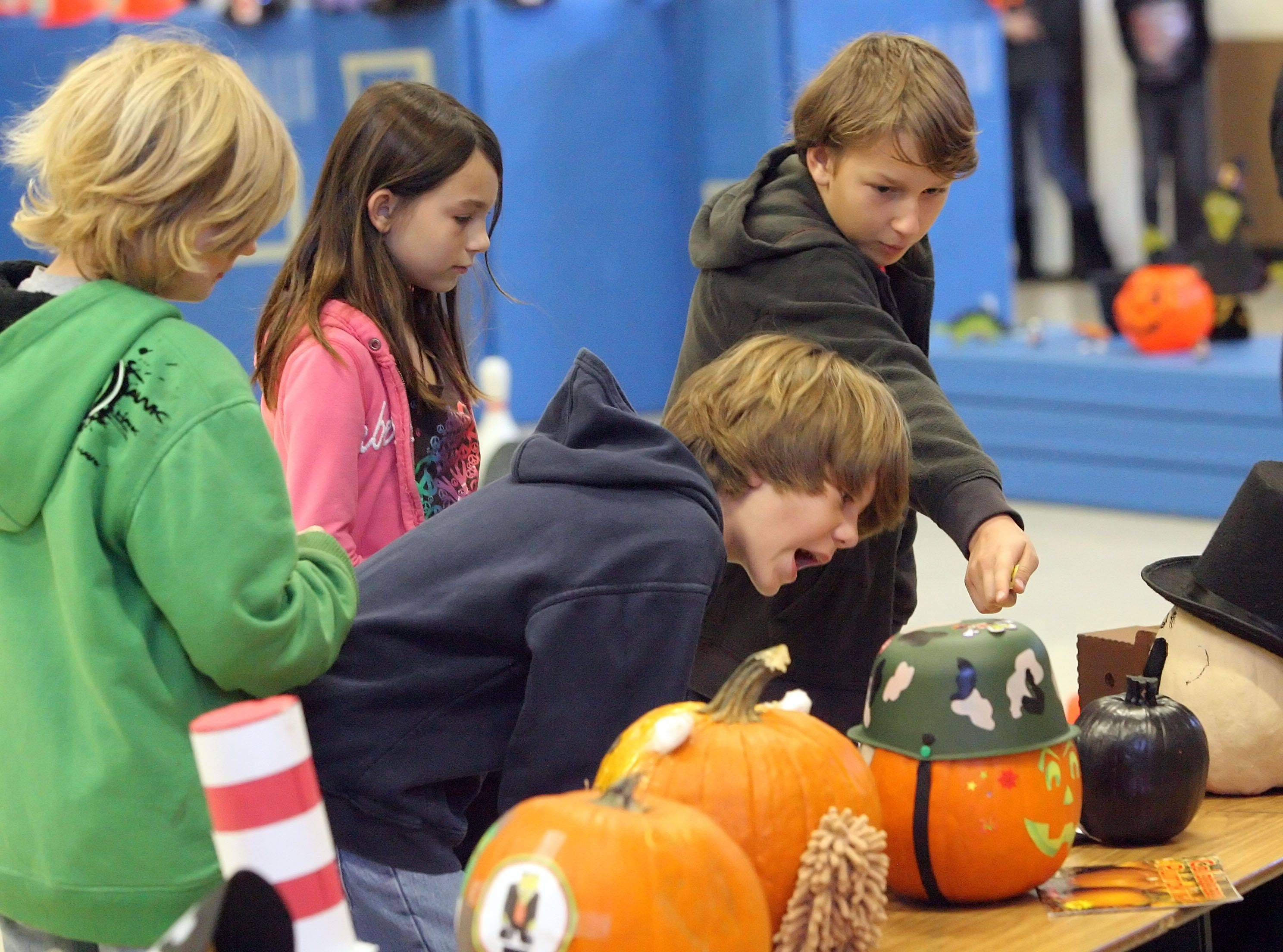 Fourth graders from left, C.J. Mitchell, Jackson Rutowski, Trinity Lemm and Alan Tondryk judge decorated pumpkins at Wauconda Grade School Friday. Students and their parents decorated the pumpkins as characters from their favorite books. The contest was sponsored by the school's literacy committee.