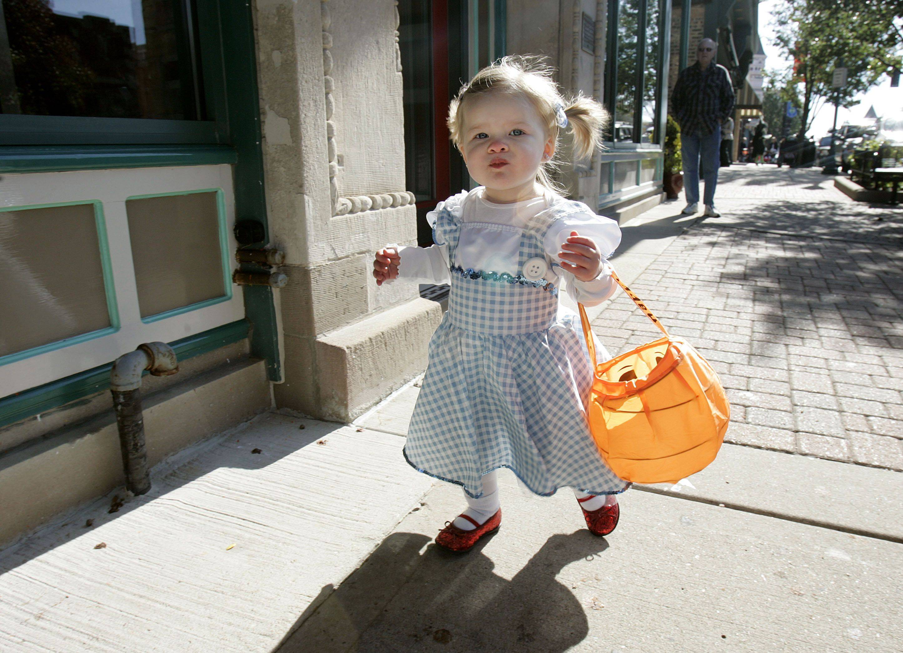 One-year-old Hailey Deuter of Libertyvile makes her way down Milwaukee Avenue as kids trick-or-treat in downtown Libertyville Friday.