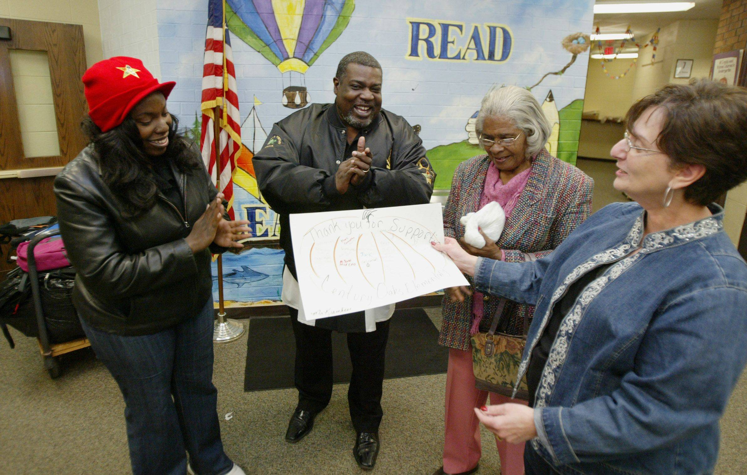 Century Oaks Elementary principal Kathy Marden presents a thank-you card to Ashanti' Harris, left, Timothy Harris and Martha Wallace Friday morning after the three brought a cart full of school supplies and gift certificates worth $500 as a donation to a classroom at the school. Third-grade teacher Jen Stotlar's class was randomly chosen to receive the supplies that were donated by the brothers of the Order of the Eastern Star Watch City Lodge #131 and the sisters of Fox Valley Chapter #137. Harris is an OES past master and Wallace is a chaplain with the group which has adopted the school and plans to continue to donate supplies to help keep classrooms stocked.