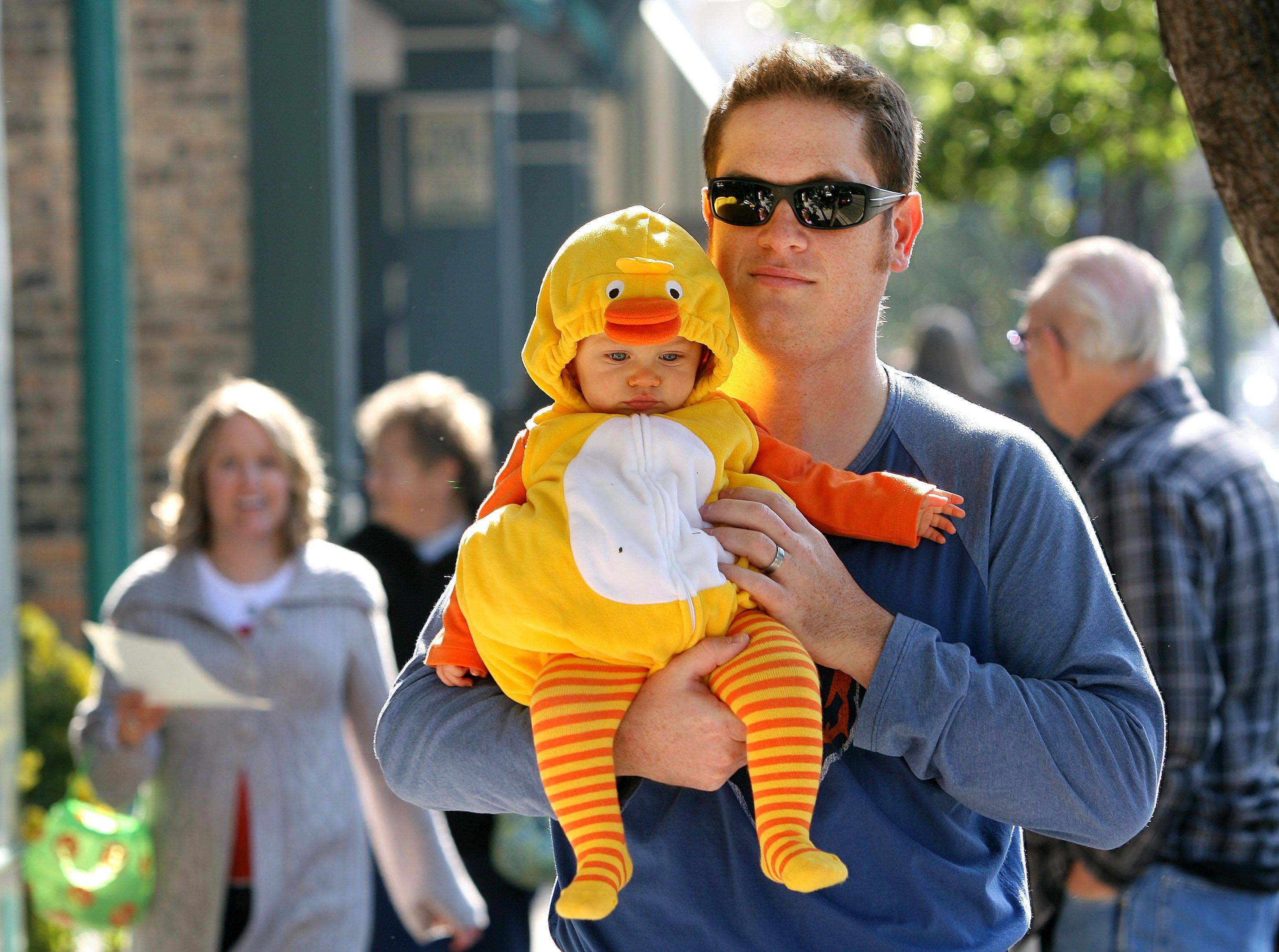 David Luacas of Grayslake holds his 10-month-old daughter Avery as they trick-or-treat on Milwaukee Avenue in downtown Libertyville Friday.