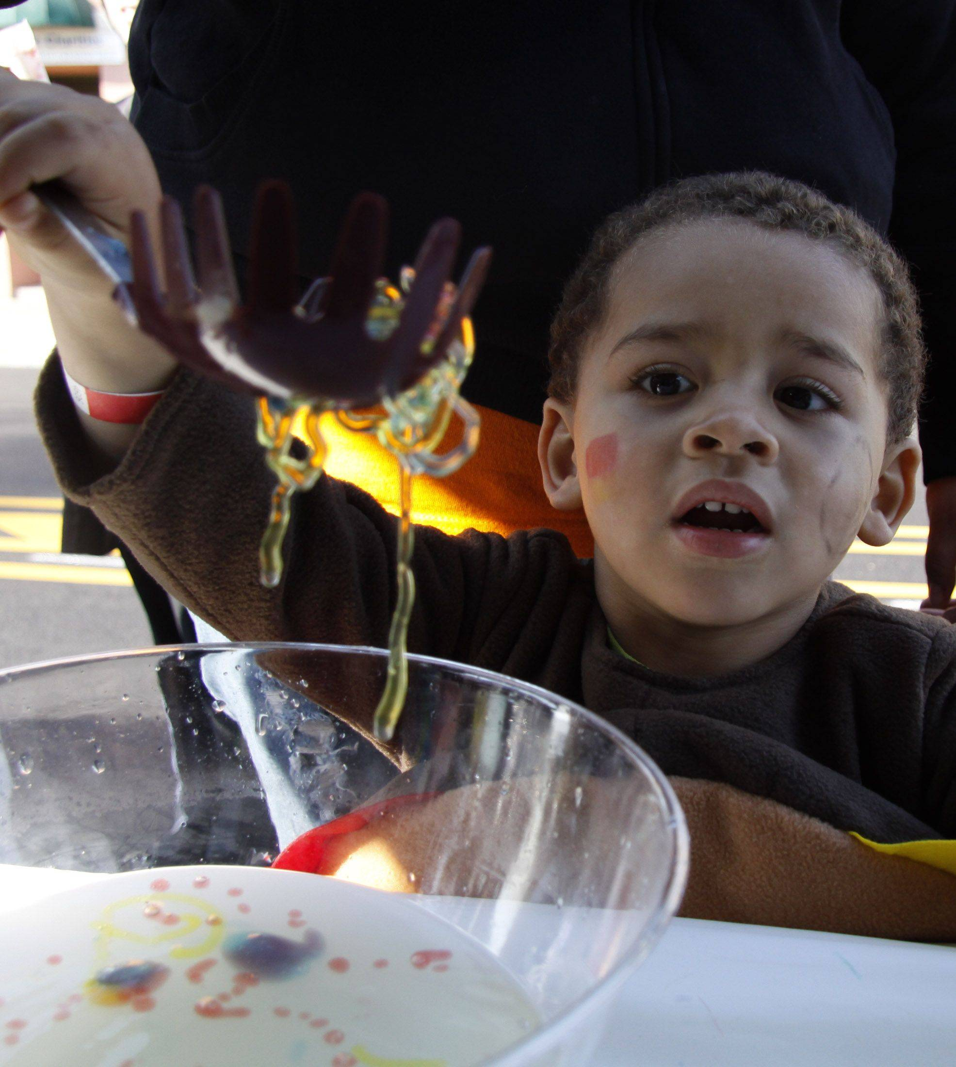 Jayden Burger, 3, of Elmhurst is amazed as he makes gooey worms at the Glenbard East High School booth at the Spooktacular Fall Festival in Lombard Saturday. The worms are a mixture of sugar from seaweed and calcium salt that causes the liquid to turn into a solid. The Key Club and National Honor Society volunteered to run the booth and help introduce science to the children.