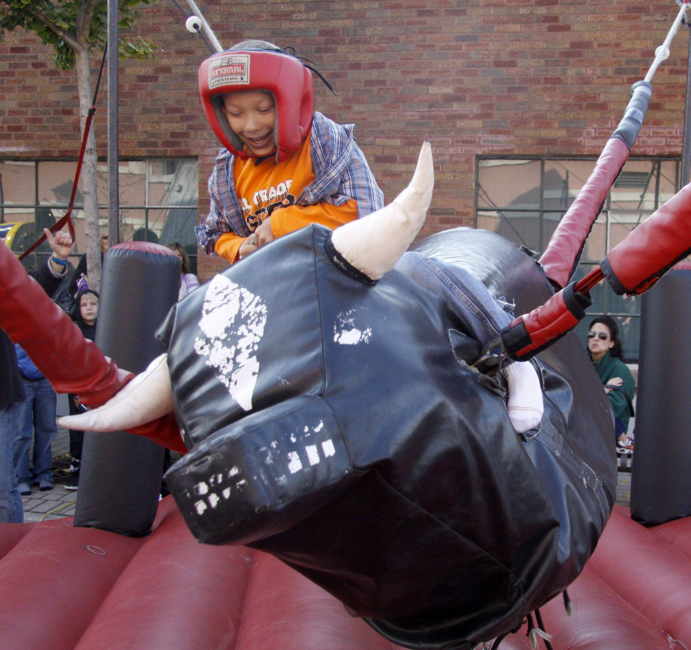 Corbin Servantez, 7, of Lombard tries to stay on the bull at the Spooktacular Fall Festival in Lombard Saturday. The event was open to the public and the town closed down the streets downtown for the event.
