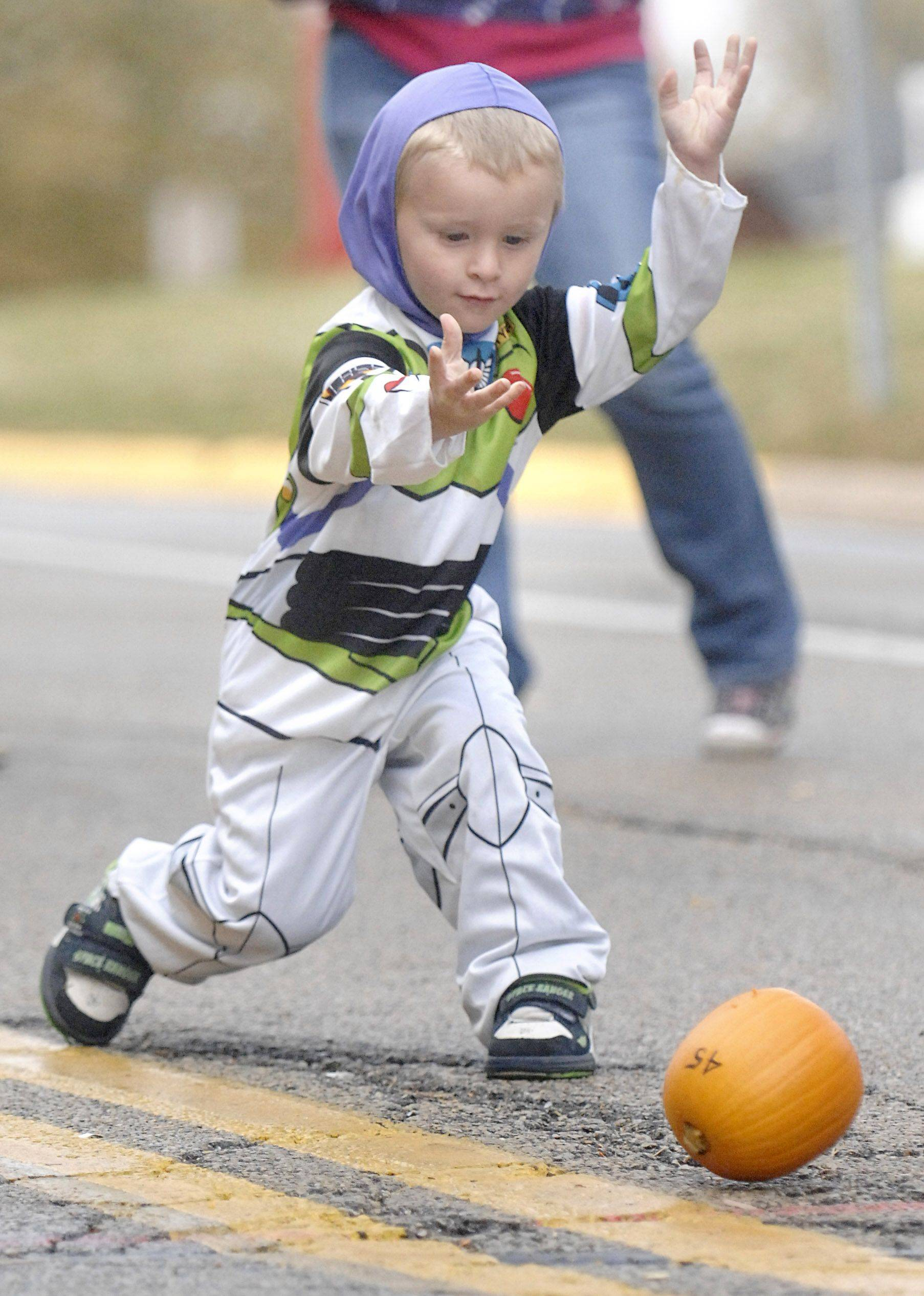 Kyle Ruhl, 3, of Batavia whips his pumpkin down Houston Street in the 10th-annual Batfest Pumpkin Roll on Saturday, October 23. People paid $1 to roll a pumpkin, and Kyle decided to do it twice. Smaller pumpkins were found to roll easier and straighter. Well, most of the time.