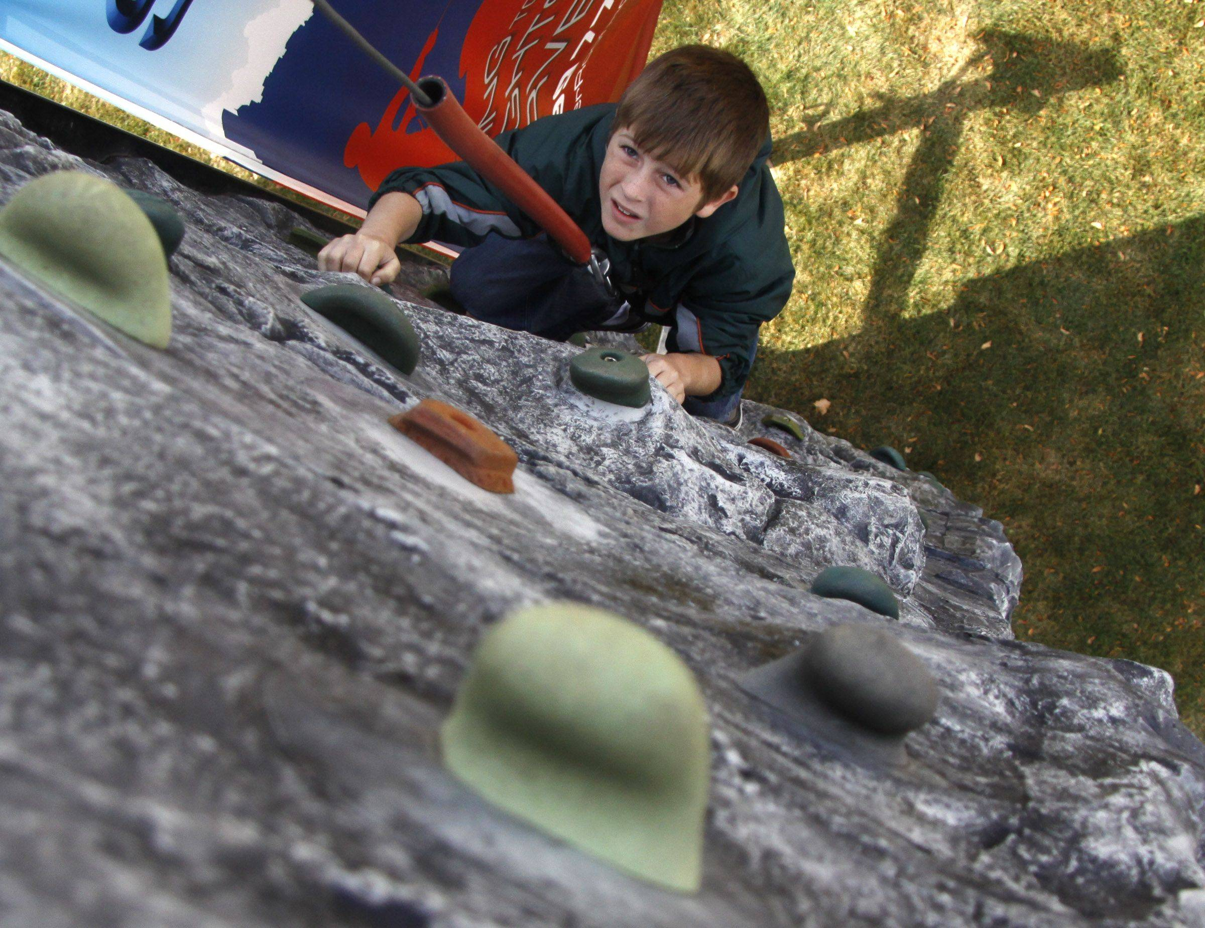 Simon Hoffman, 8 of Wheaton climbs the 32-foot climbing wall at Make a Difference Day in Wheaton.