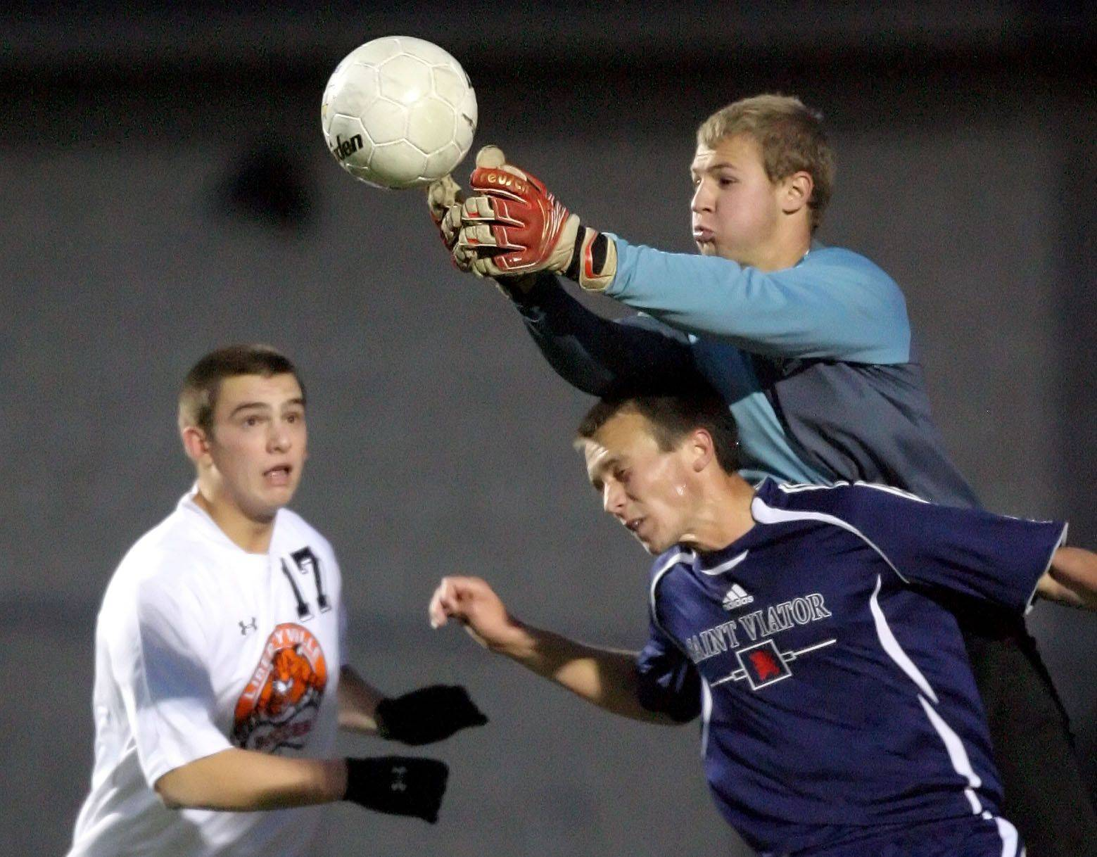 St. Viator goalie Scott Faul jumps over the back of teammate Joe Surdam to make the save as Libertyville's Austin Bitta looks on during the class 3A sectional semifinal at Libertyville High School Wednesday.