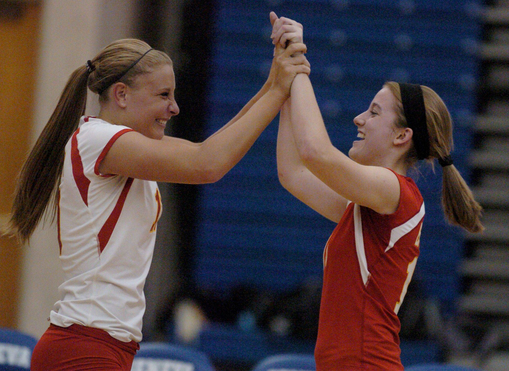 Batavia teammates, Caitlin Piechota and Stephanie Kinane, high five after defeating Metea Valley for their second win at the IHSA Regional Volleyball game at Geneva High School Thursday evening.