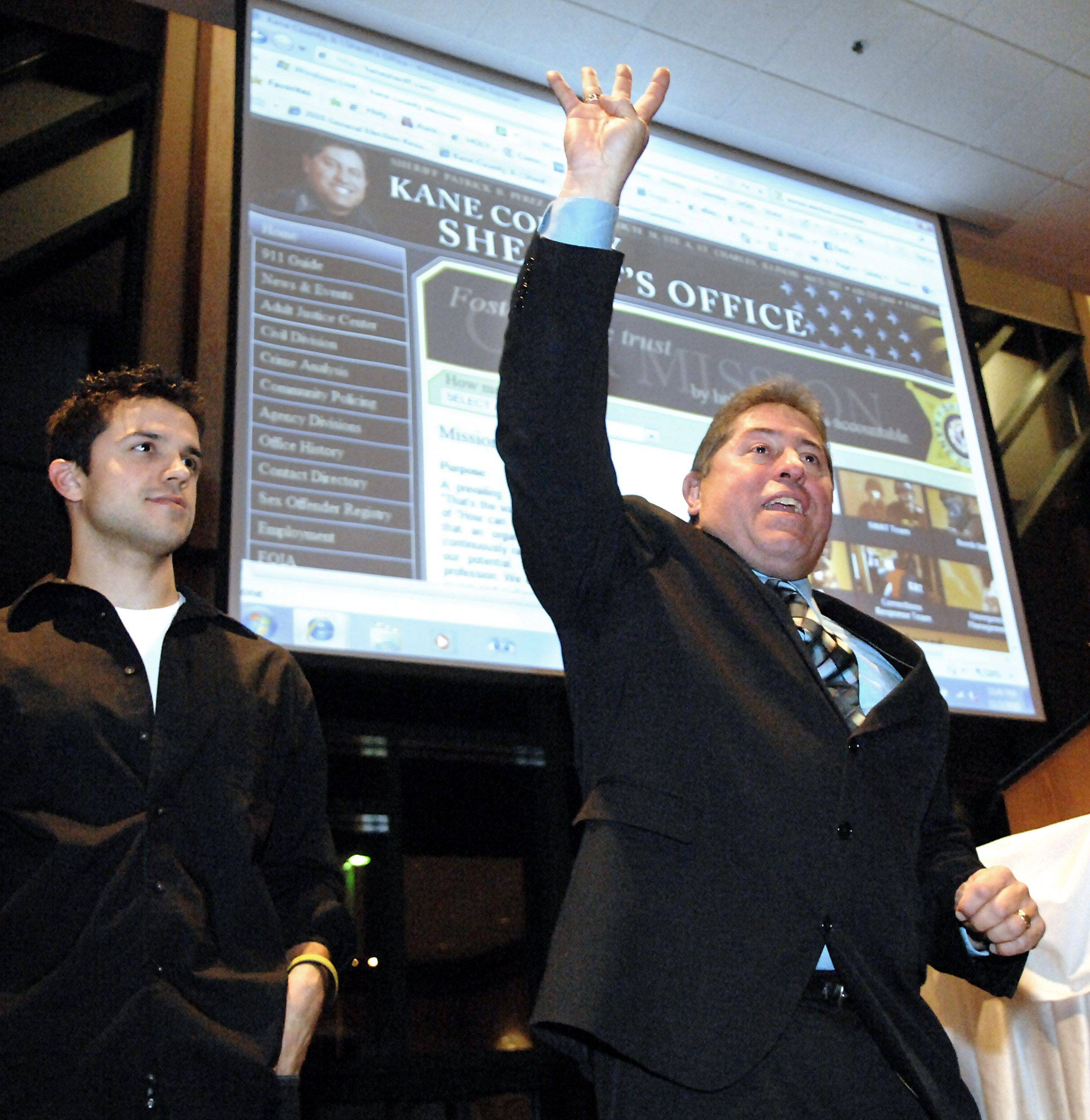 "With son Stephan by his side, Kane County Sheriff Pat Perez holds up four fingers and says, ""Four more years,"" while celebrating his re-election at Piper's Banquets in Aurora on Tuesday. Perez thanked his wife, Terrie, and two sons, Gabe and Stephan, along with all his supporters. He also said it would be his last term."