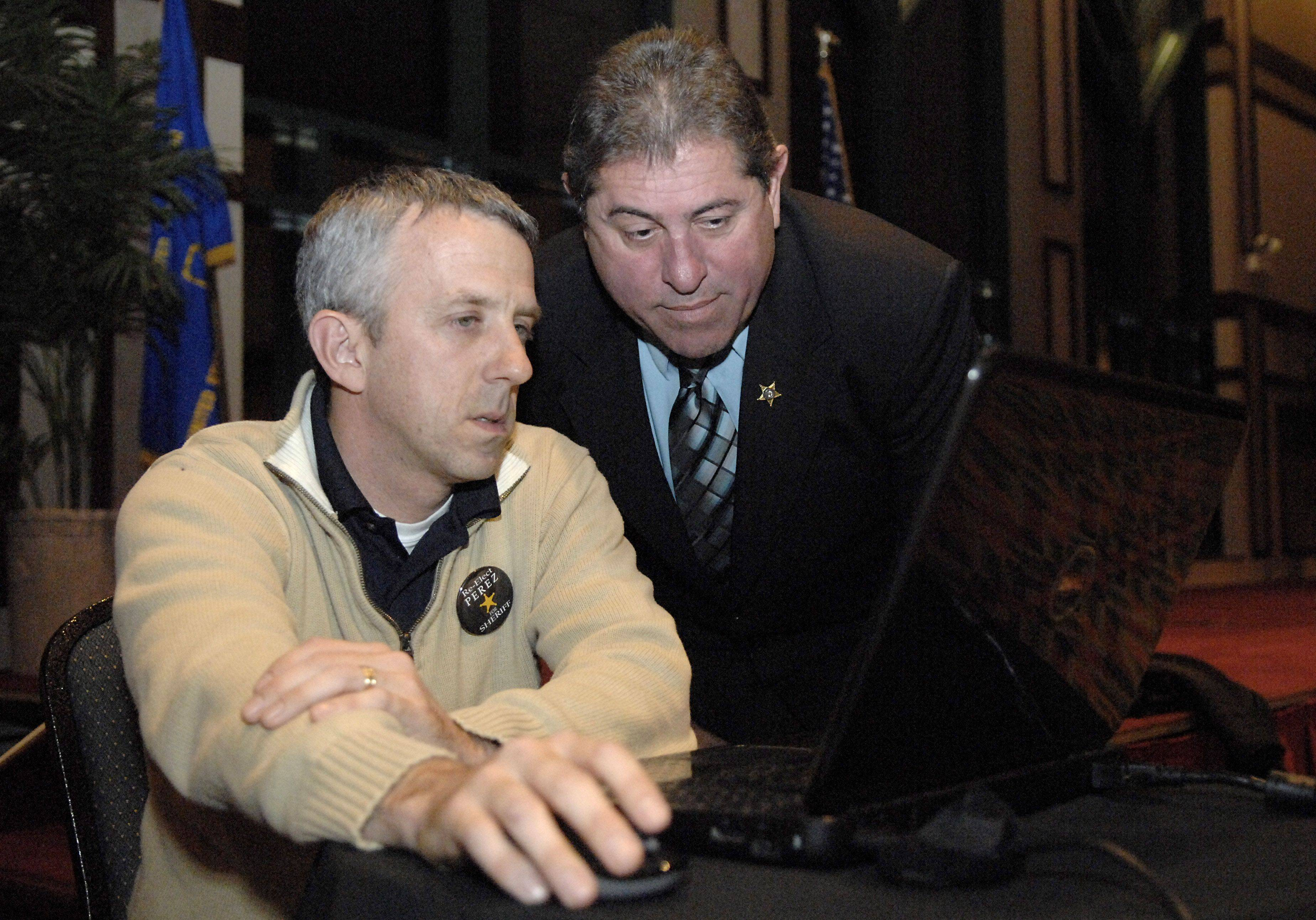Lt. Pat Gengler and Kane County Sheriff Pat Perez watch the first election results come in Tuesday in Aurora.