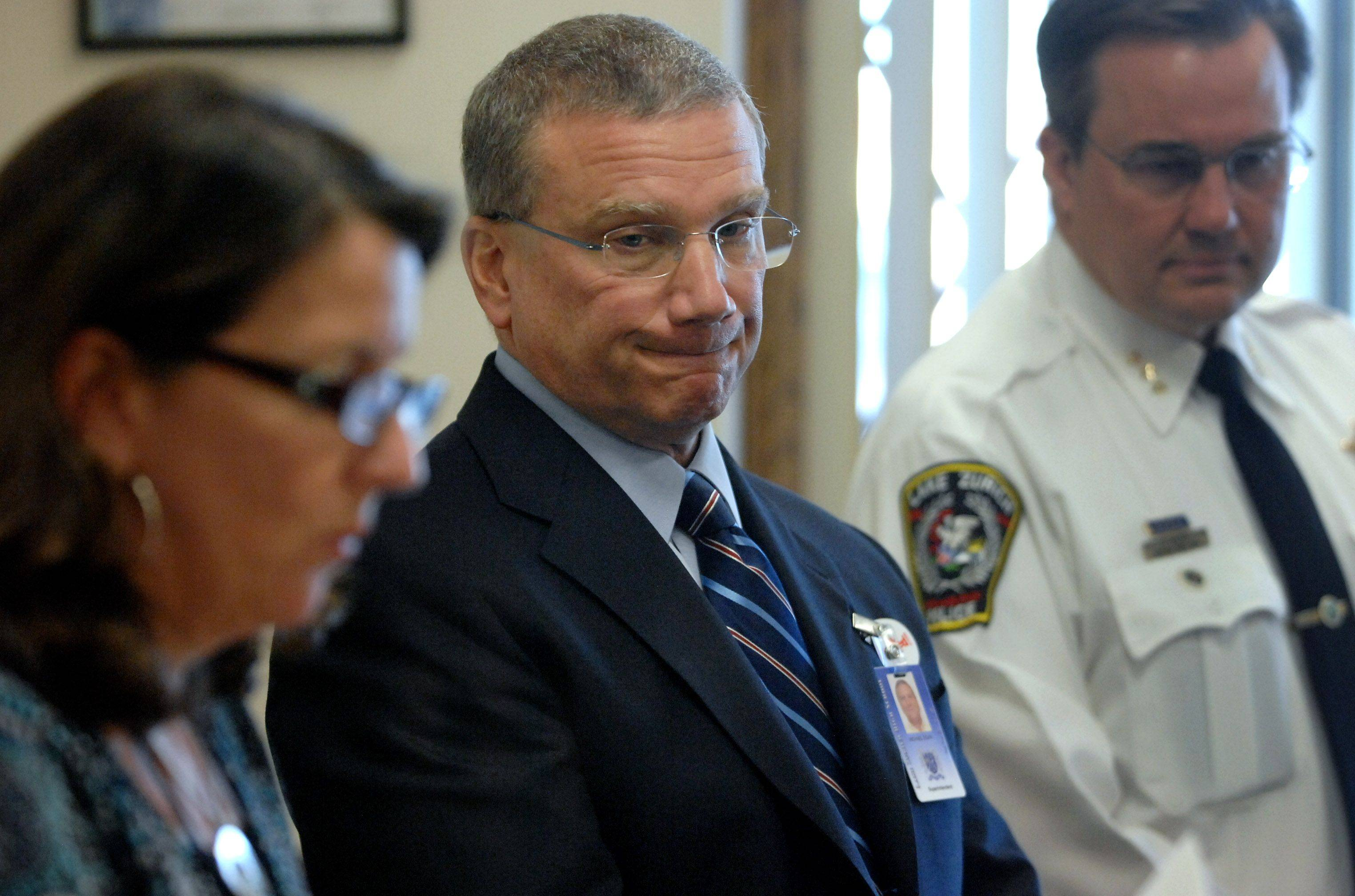Lake Zurich Unit District 95 spokeswoman Jean Malek, left, addresses the media Tuesday regarding the arrest of Ronald D. Culver, who taught at the district's high school. Superintendent Michael Egan, center, and police Chief Patrick Finlon listen to Malek.