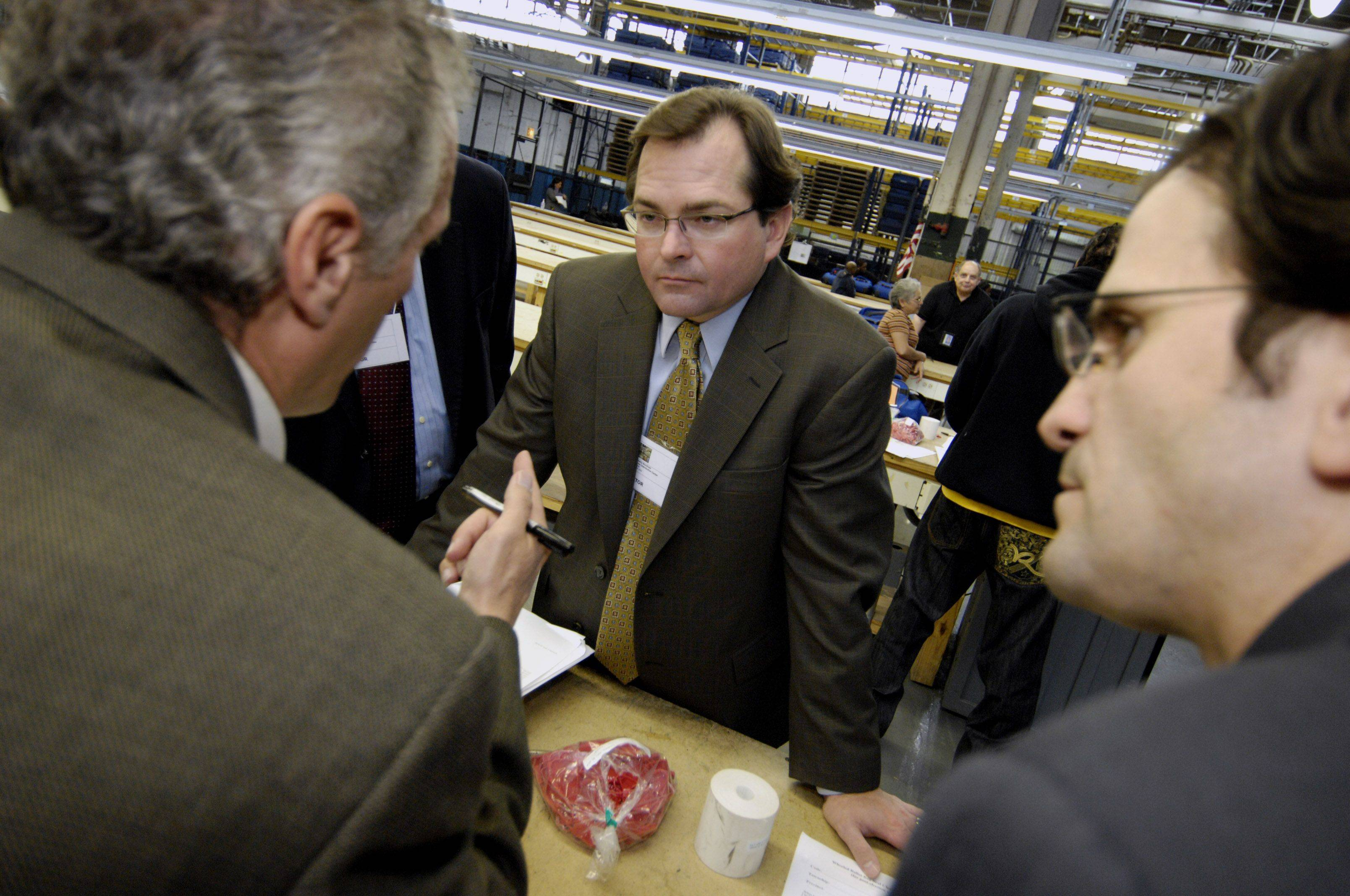 General Counsel for the Illinois Republican Party, Brien Sheahan talks with Joe Walsh representatives Nick and Chris Provenzano as election ballots from Cook County are counted at the Cook County Clerk Election Warehouse in Chicago. Sheahan was representing the entire Republican party including Governor candidate Bill Brady.
