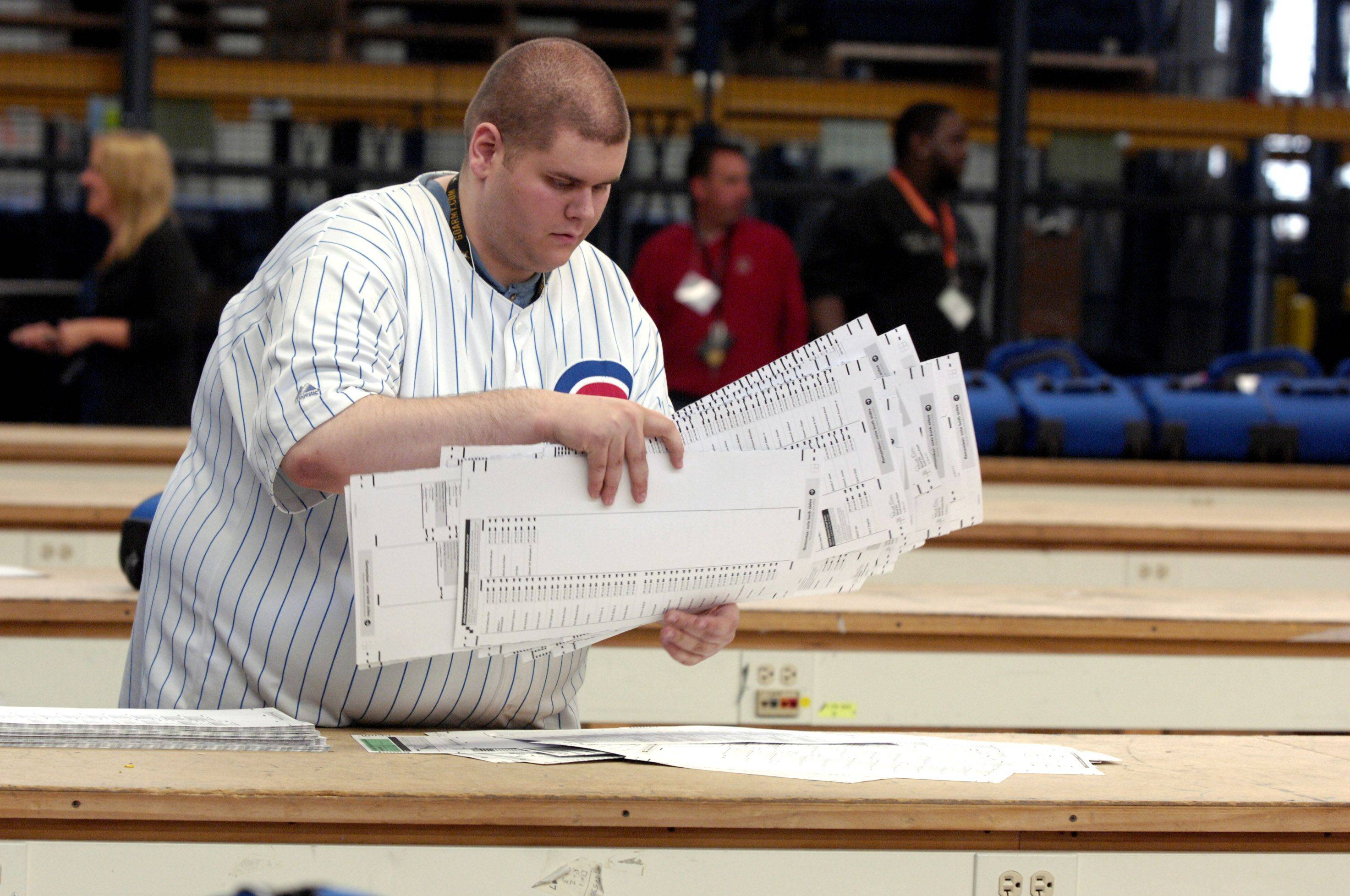 Danny Roberts stacks election ballots from Cook County before they are counted at the Cook County Clerk Election Warehouse in Chicago.