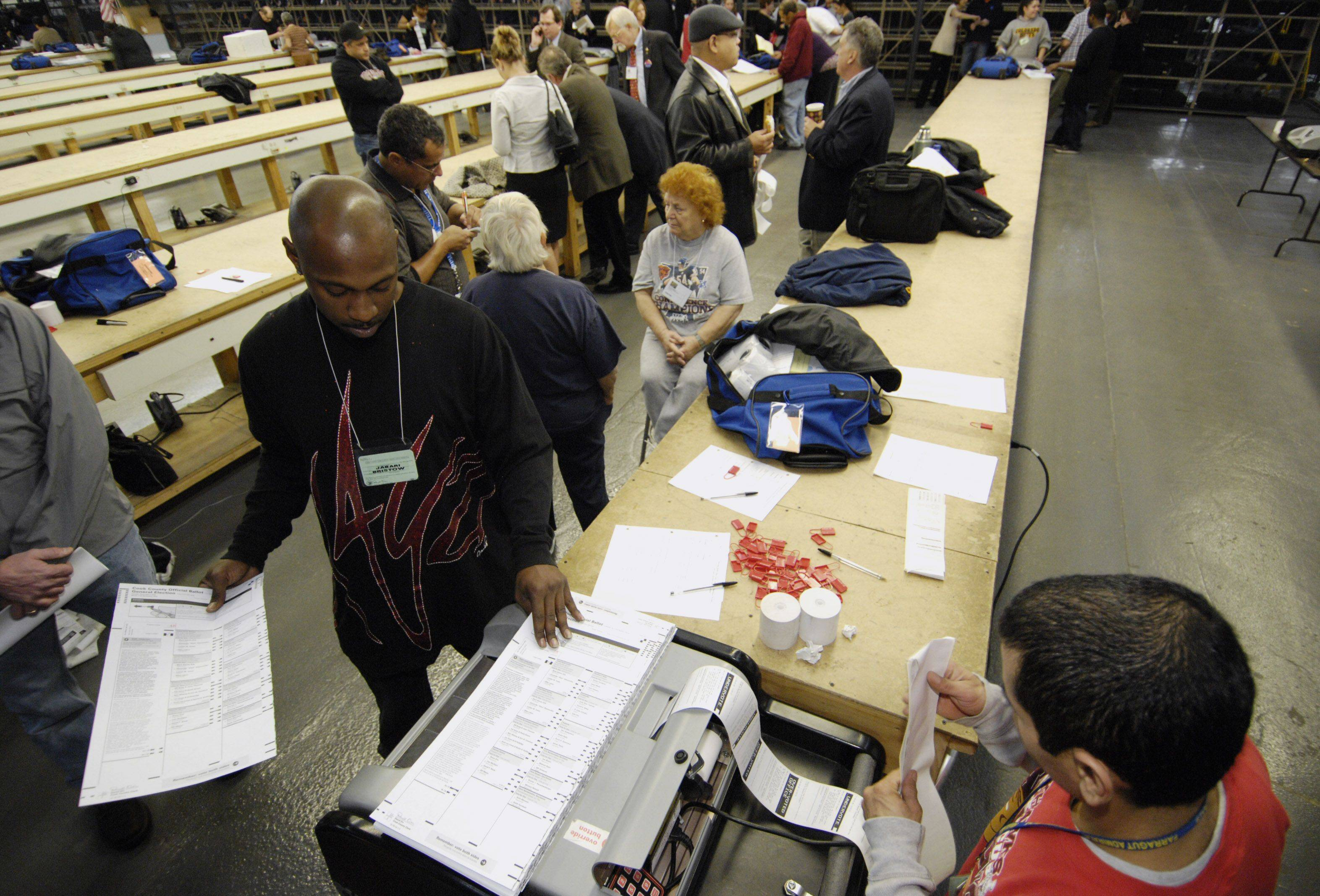 Jabari Bristow and Juan Robles count election ballots from Cook County at the Cook County Clerk Election Warehouse in Chicago.