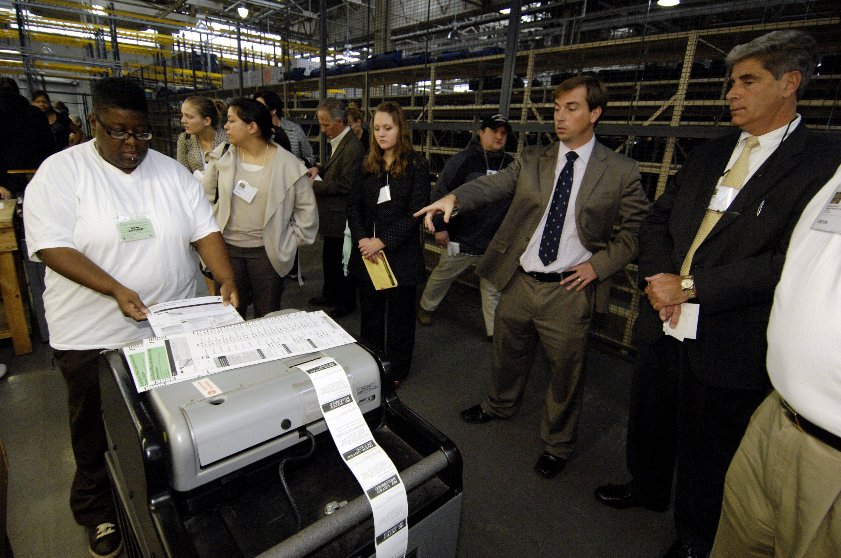 Kim Oliver runs election ballots from the Schaumburg #2 precinct through the counter at the Cook County Clerk Election Warehouse in Chicago as clerk and candidate representative look on.