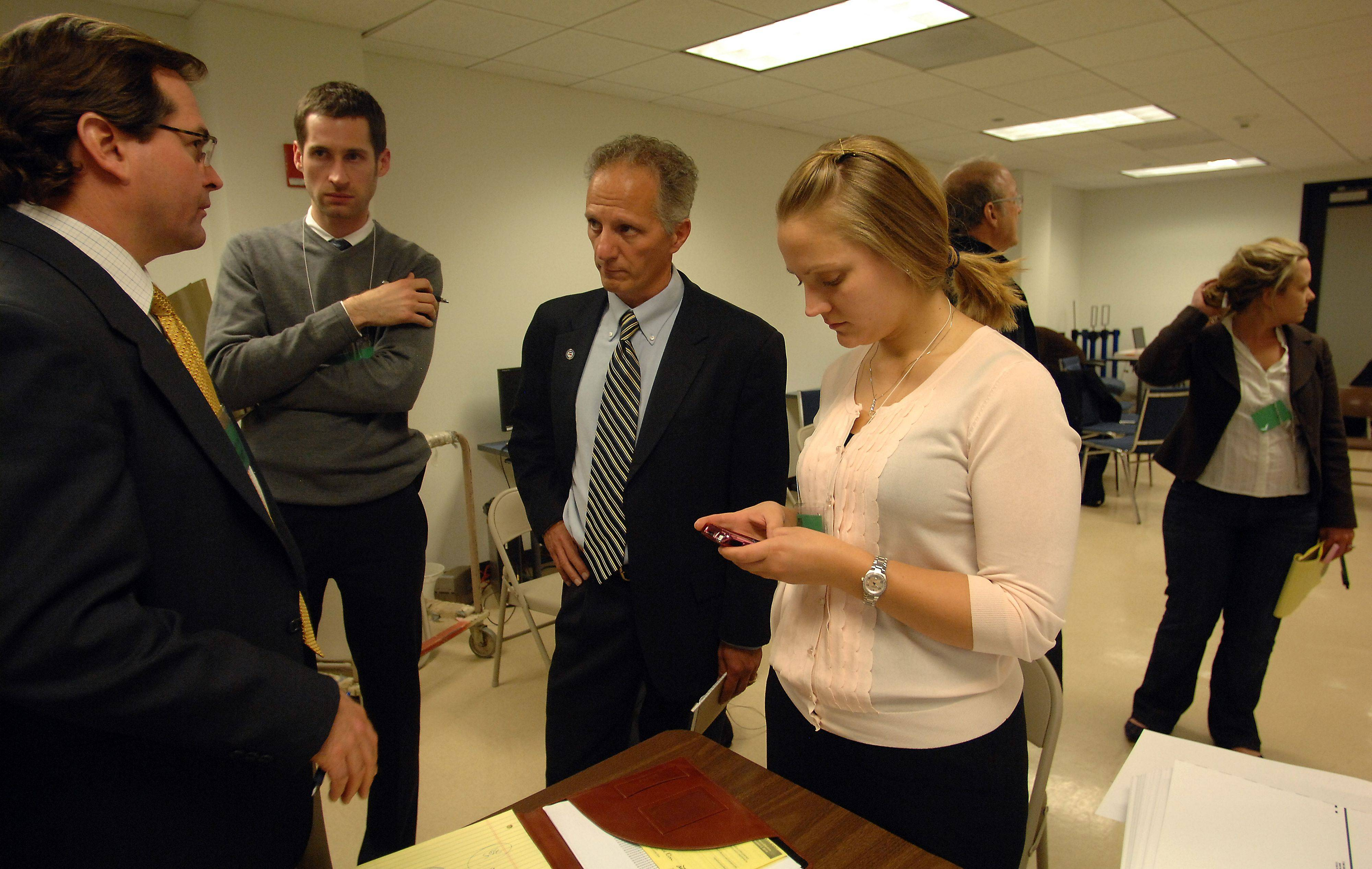 Republican attorney Brien Sheahan (left) talks with Brian Neale, Legislative Counsel from Washington D.C., Joe Walsh campaign manager Nick Provenzano and Kristina Hanson, attorney for the Walsh camp, about the absentee ballots being counted in Chicago on Thursday. In the background are members of the Melissa Bean camp.