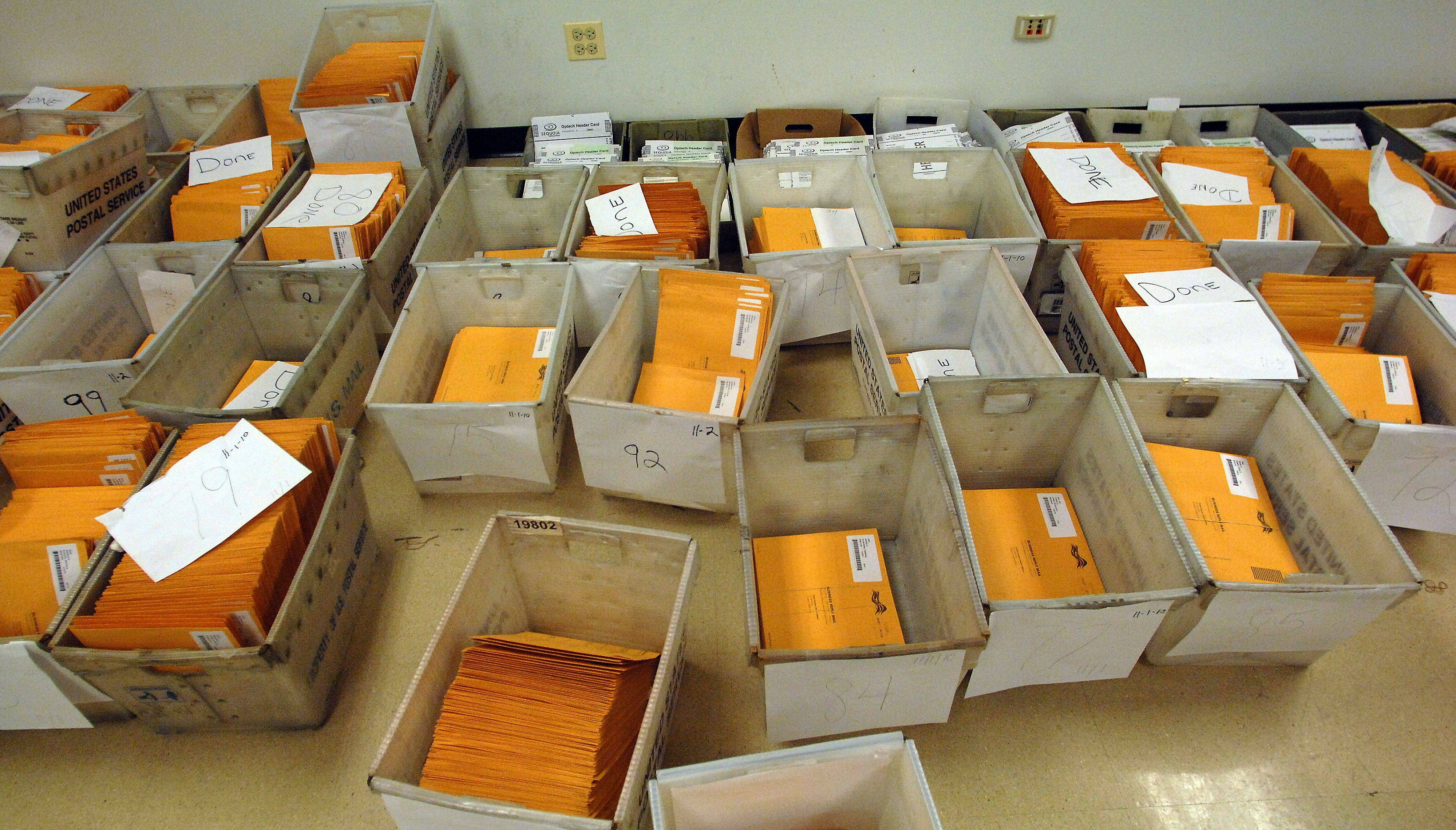 Boxes of absentee ballots lie on the floor as the counting continued Thursday in the 8th Congressional District race.