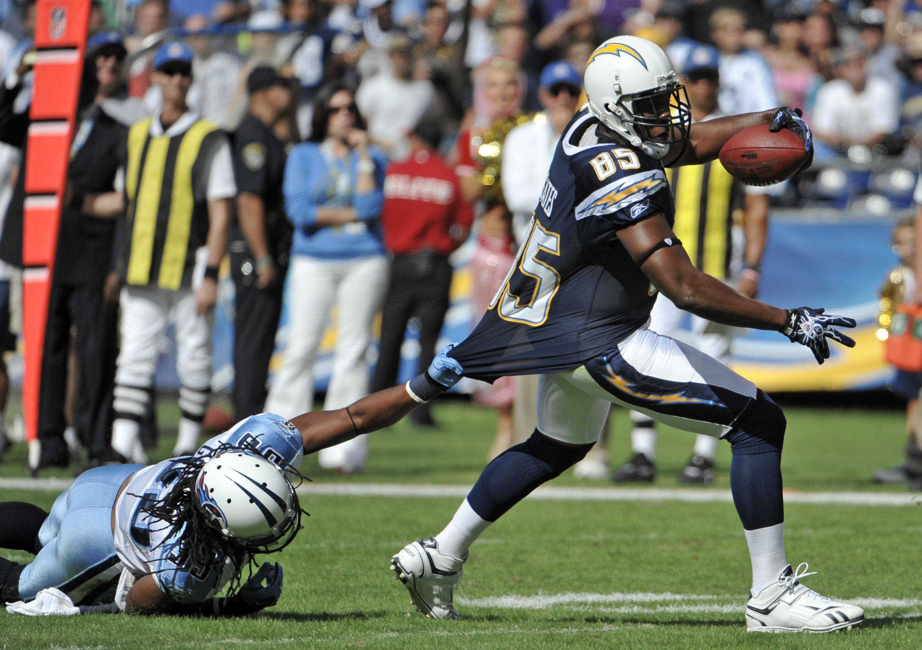San Diego Chargers tight end Antonio Gates (85) drags Tennessee Titans safety Michael Griffin, left, while gaining 15 yards on a pass-completion during the first half of an NFL football game on Oct. 31 in San Diego.