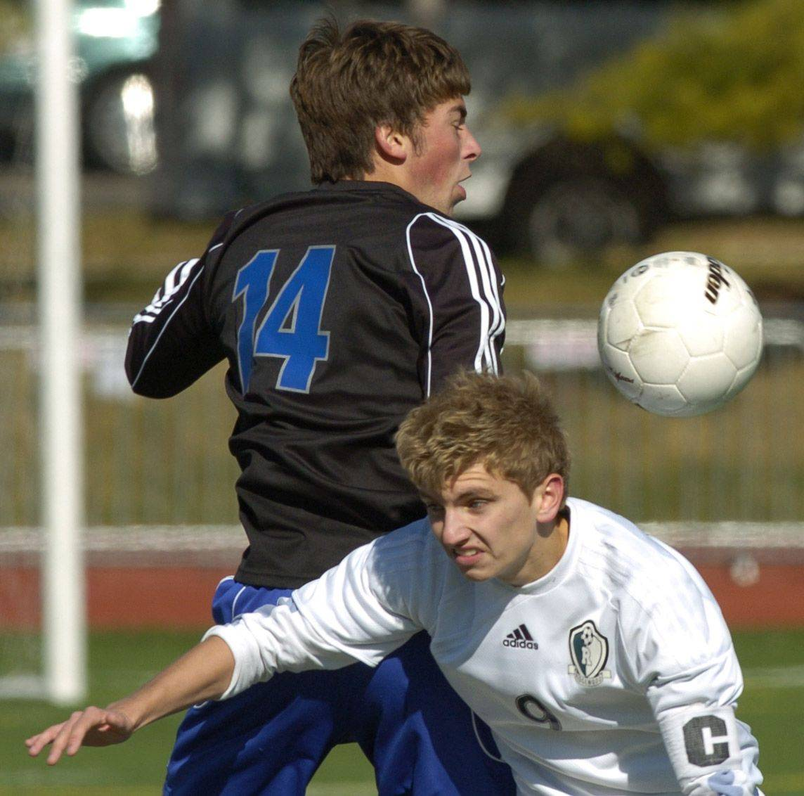Burlington Central's Brandon Cesaroni, left, and Ridgewood's Peter Soja try to control the ball.