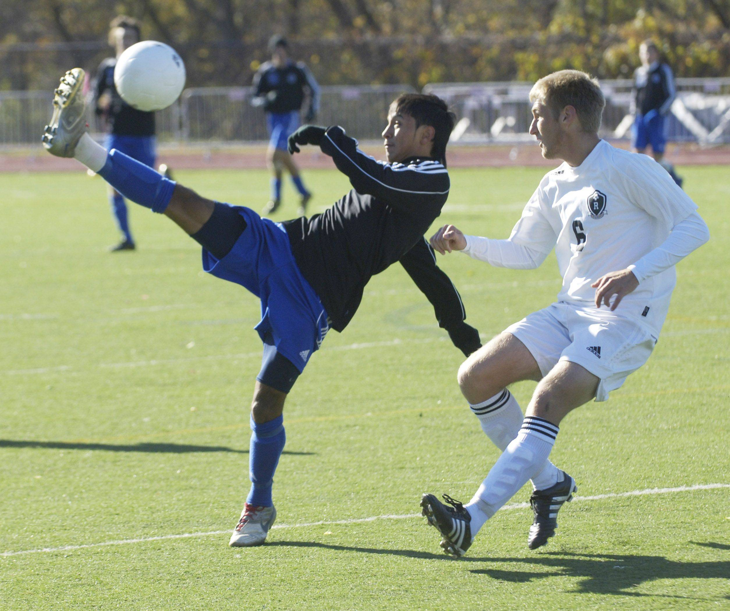 Alexis Camarena of Burlington Central, left, kicks high to direct the ball past Ridgewood's Mike Kuczek .