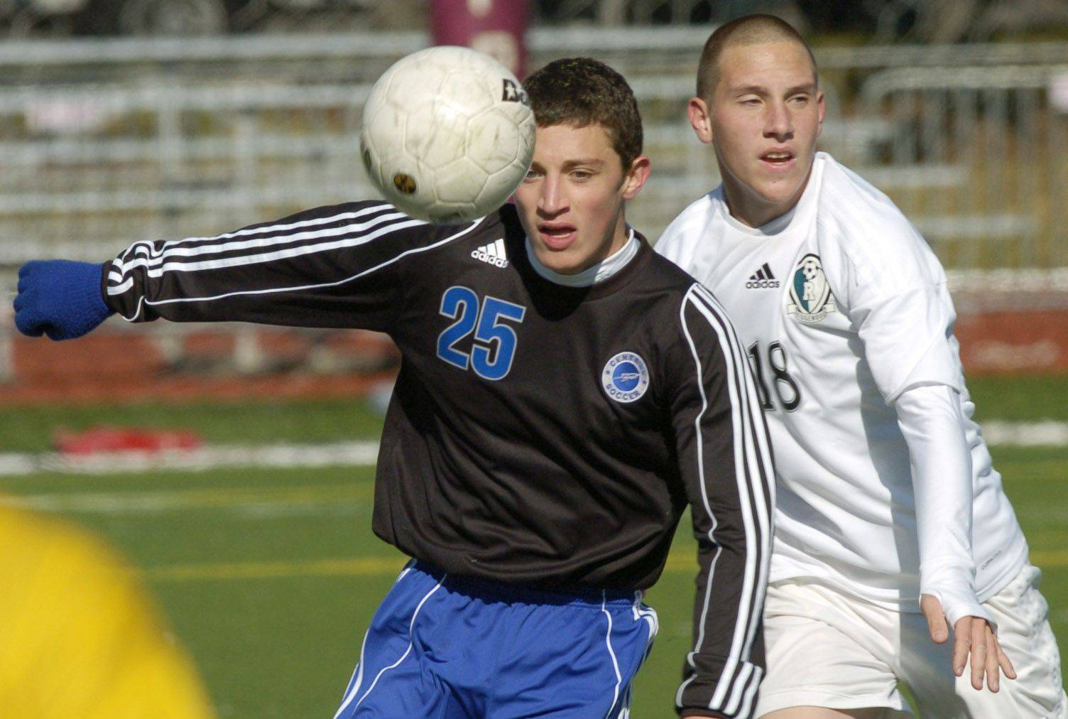The ball bounces in front of Burlington Central's Brad Herron, left, and Ridgewood's Rafal Maslowski.