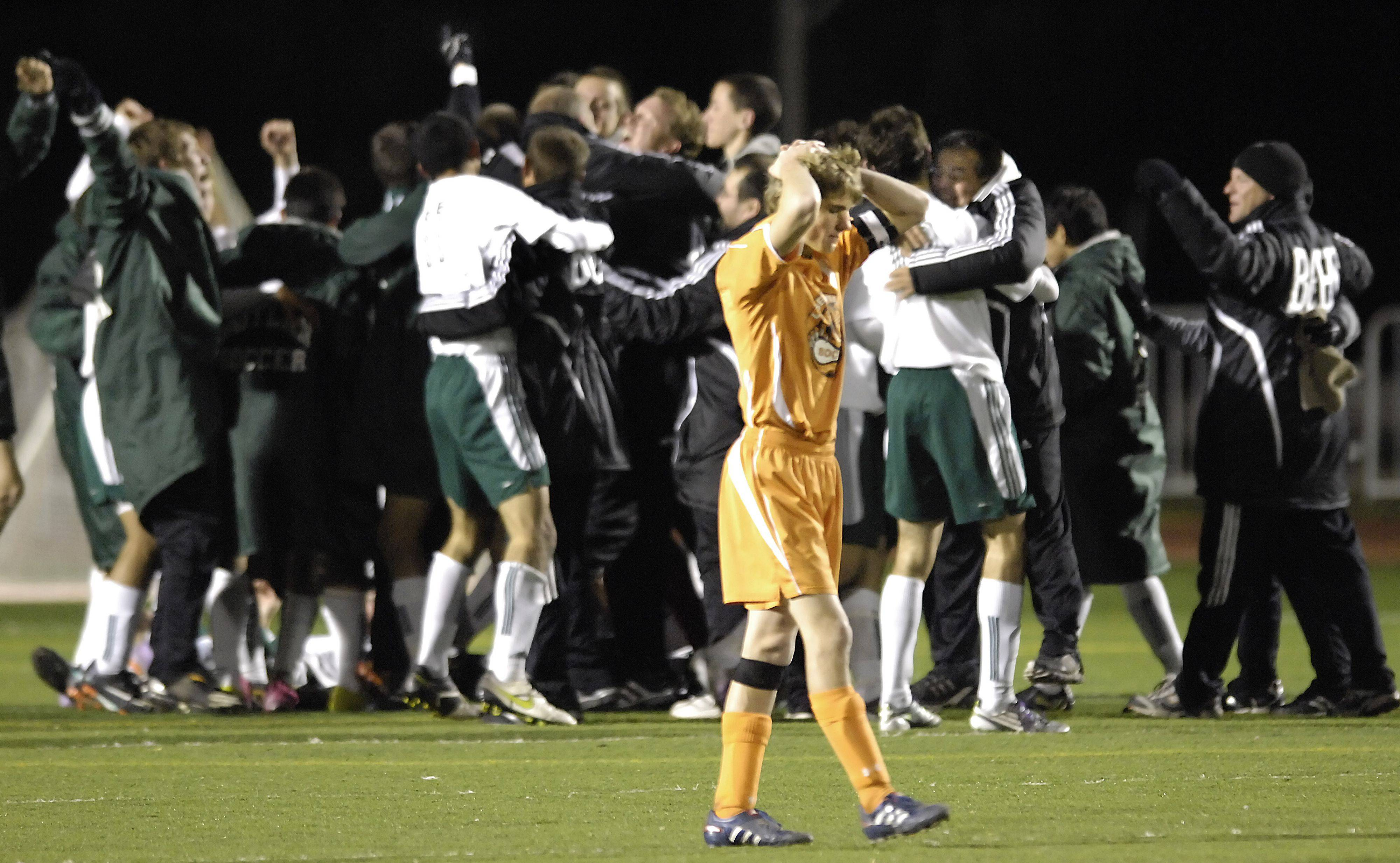 Libertyville's Marshall Hollingsworth walks away with his hands on his head as Rockford Boylan celebrates the state championship in Naperville Saturday.