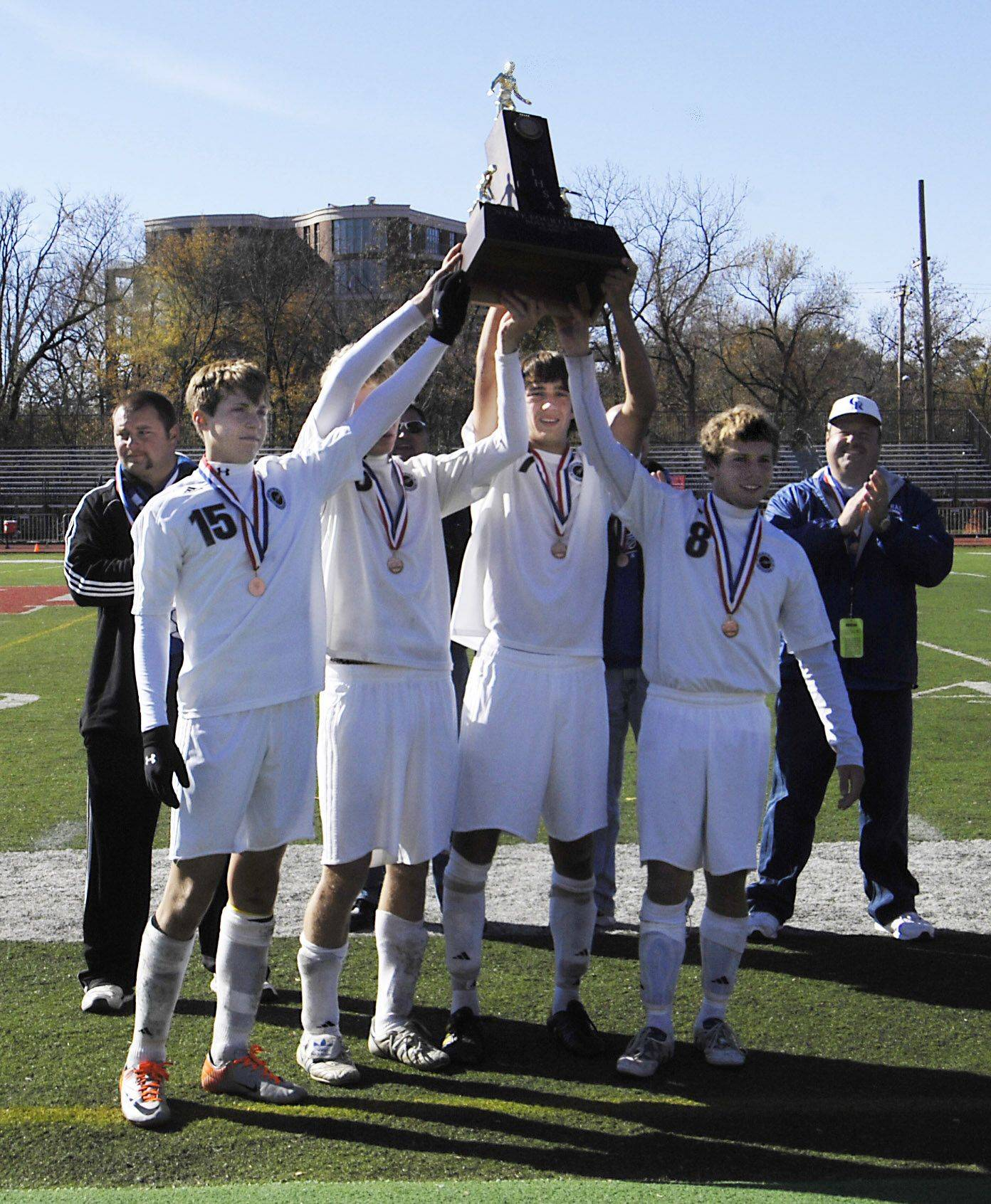 Burlington Central captains Bryce Warner, Zachary Jochum, Kyle Reopelle and Christopher Gousios hold the fourth place trophy in the state tournament in Naperville Saturday.