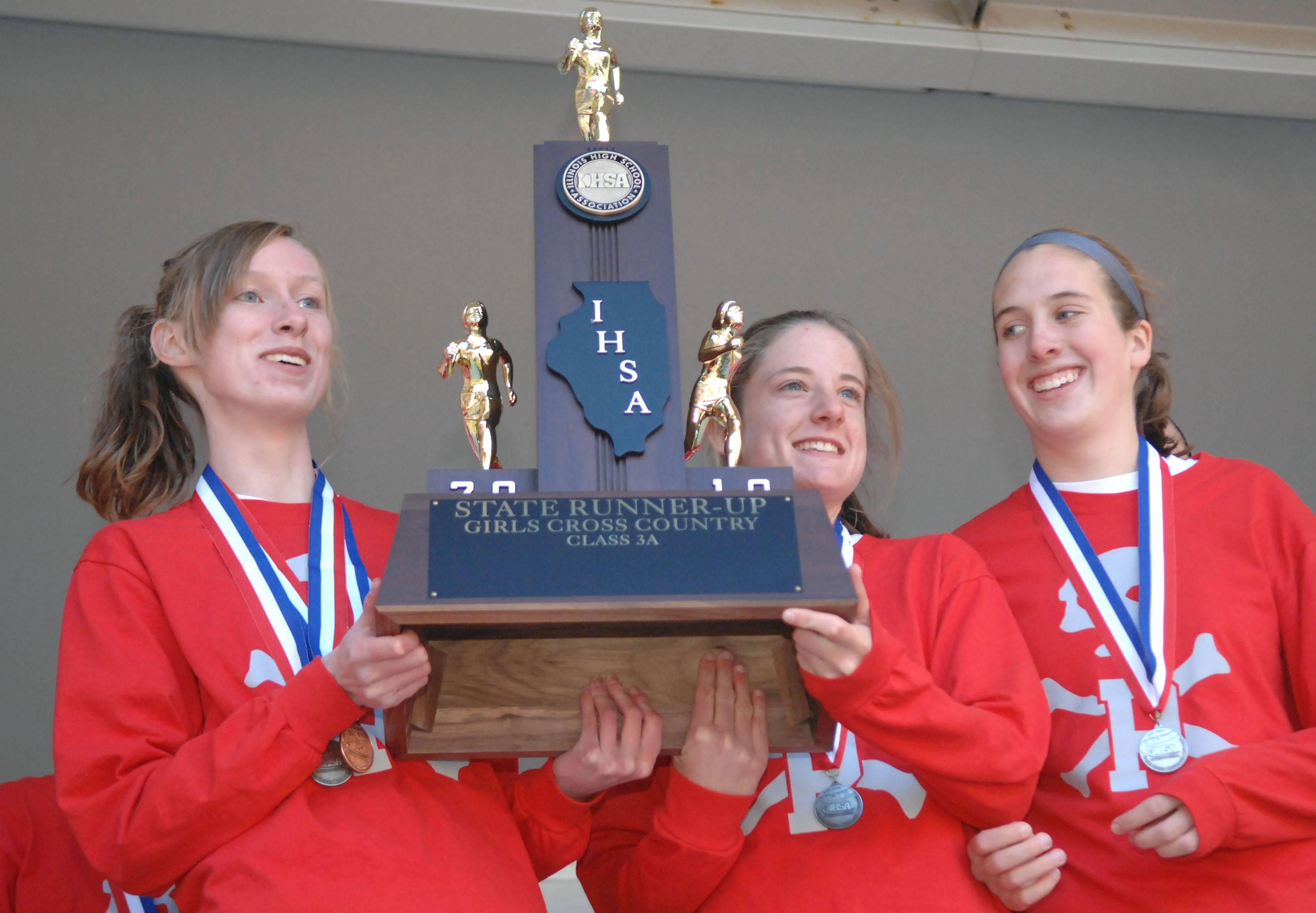 Palatine's Courtney Brown, Sarah McIntosh and Becca Sund accept their team's second place cross country 3A state trophy at Detweiller Park in Peoria on Saturday, November 6.