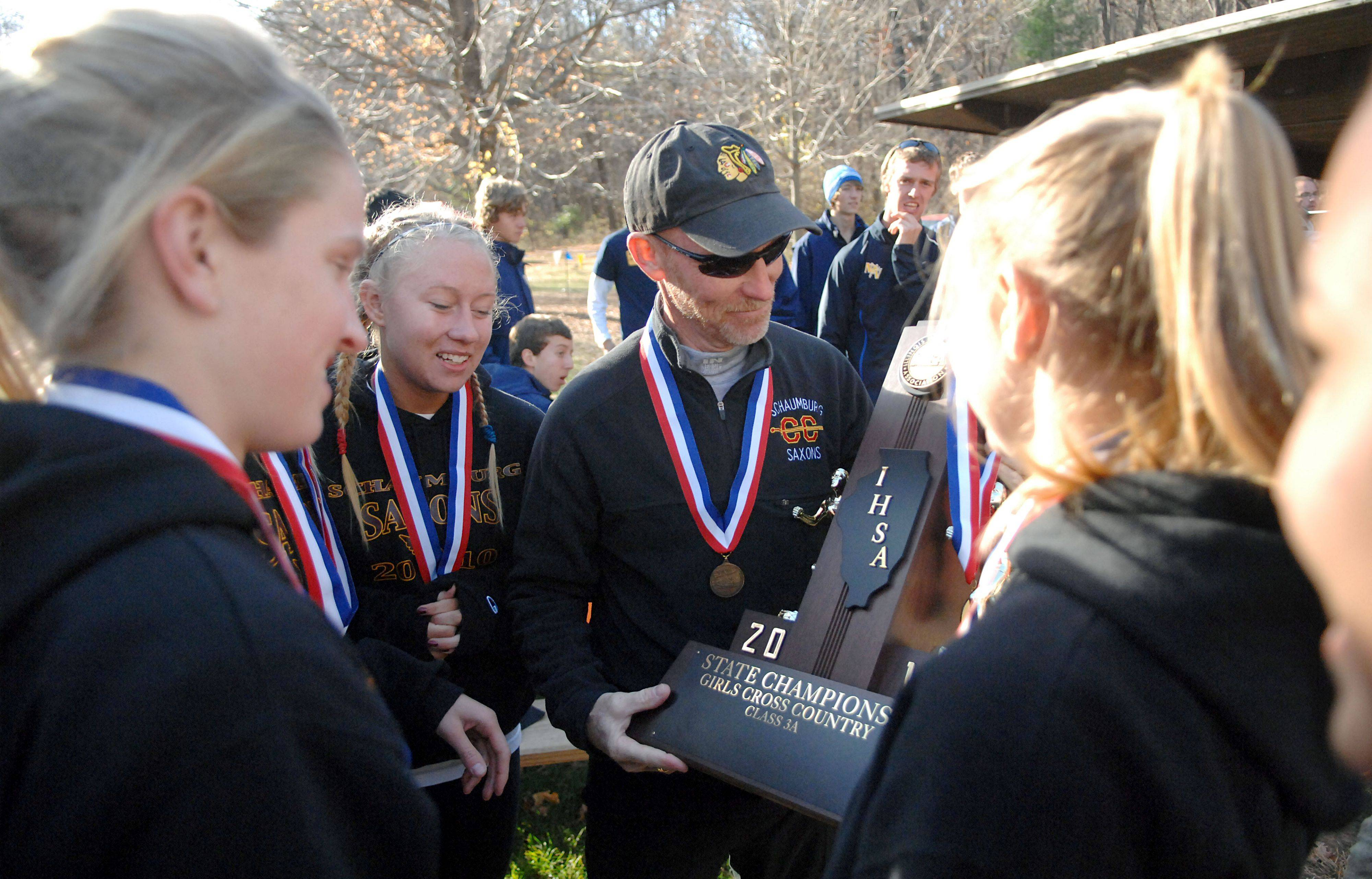 Schaumburg head coach Jon Macnider smiles as the girls hand him their first place 3A cross country state trophy after the awards assembly at Detweliler Park in Peoria on Saturday, November 6.