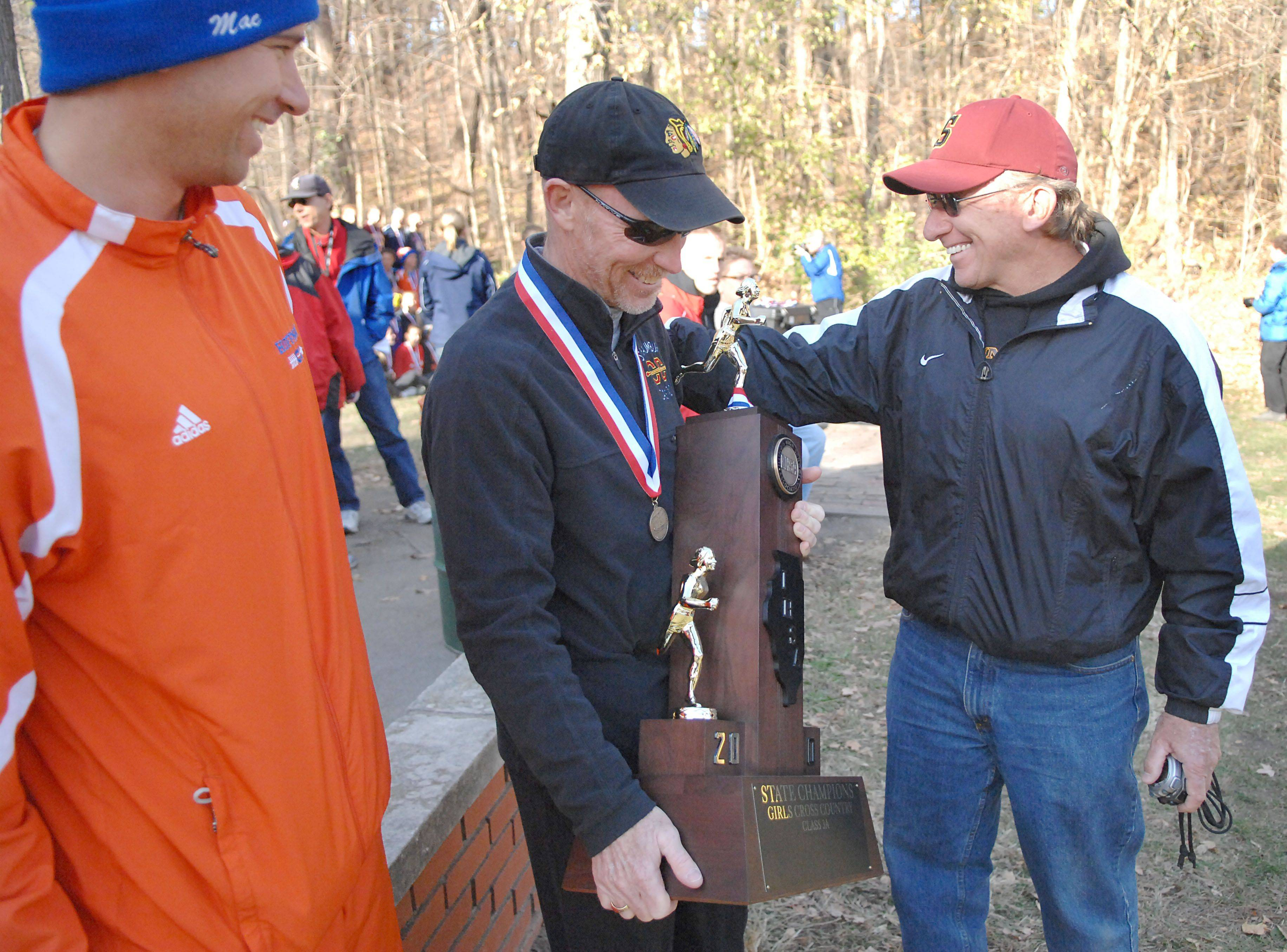 Schaumburg head coach Jon Macnider, center, is congratulated by brother, Jim, right, after winning the first place 3A cross country trophy in Peoria on Saturday, November 6. On left is Jim's son, Kirk Macnider, who coaches at Hoffman Estates.