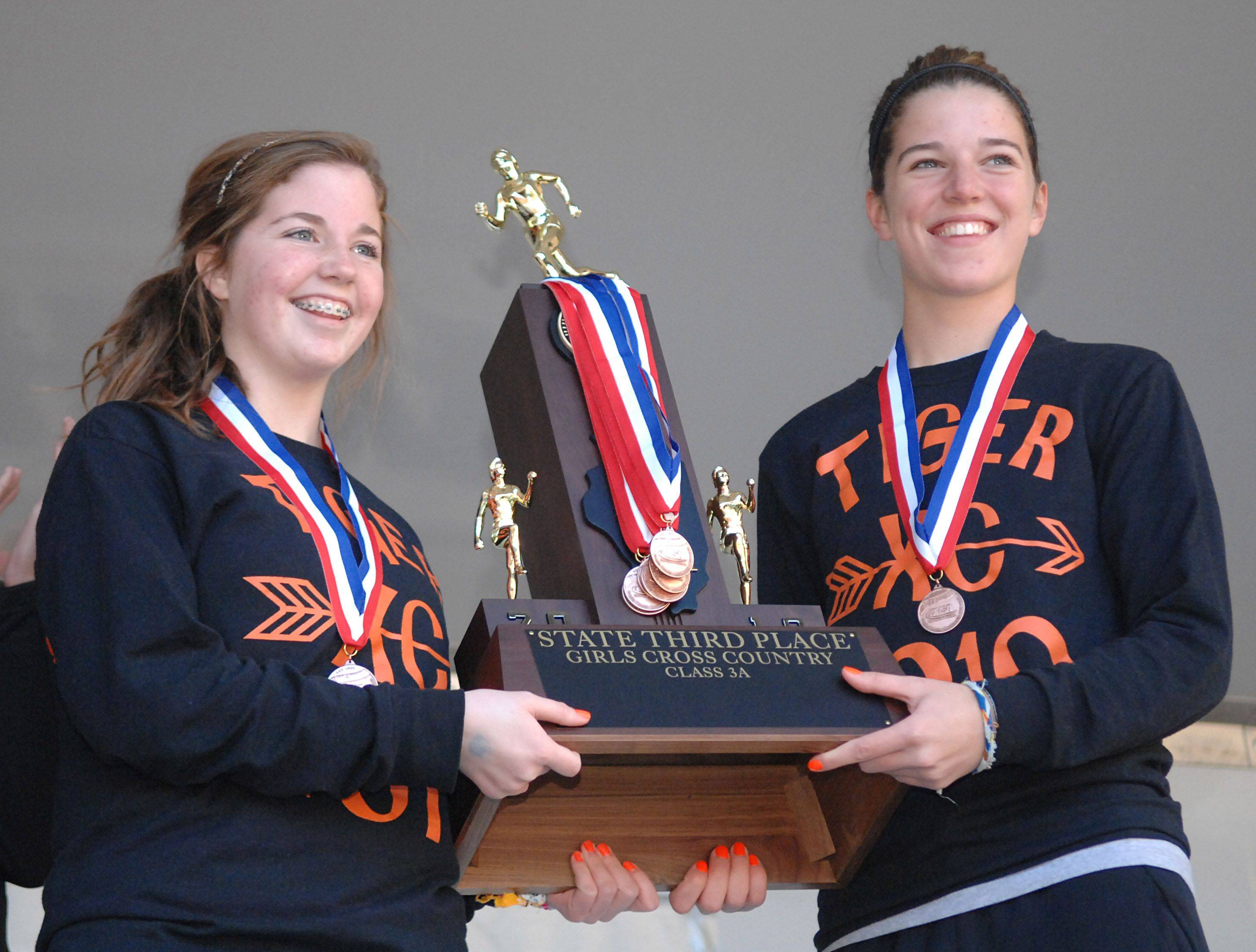 Warrenville South's Bridget Kelly, left, and Maddie Williams, both seniors, accept their team's third place cross country 3A state trophy in Peoria on Saturday, November 6.