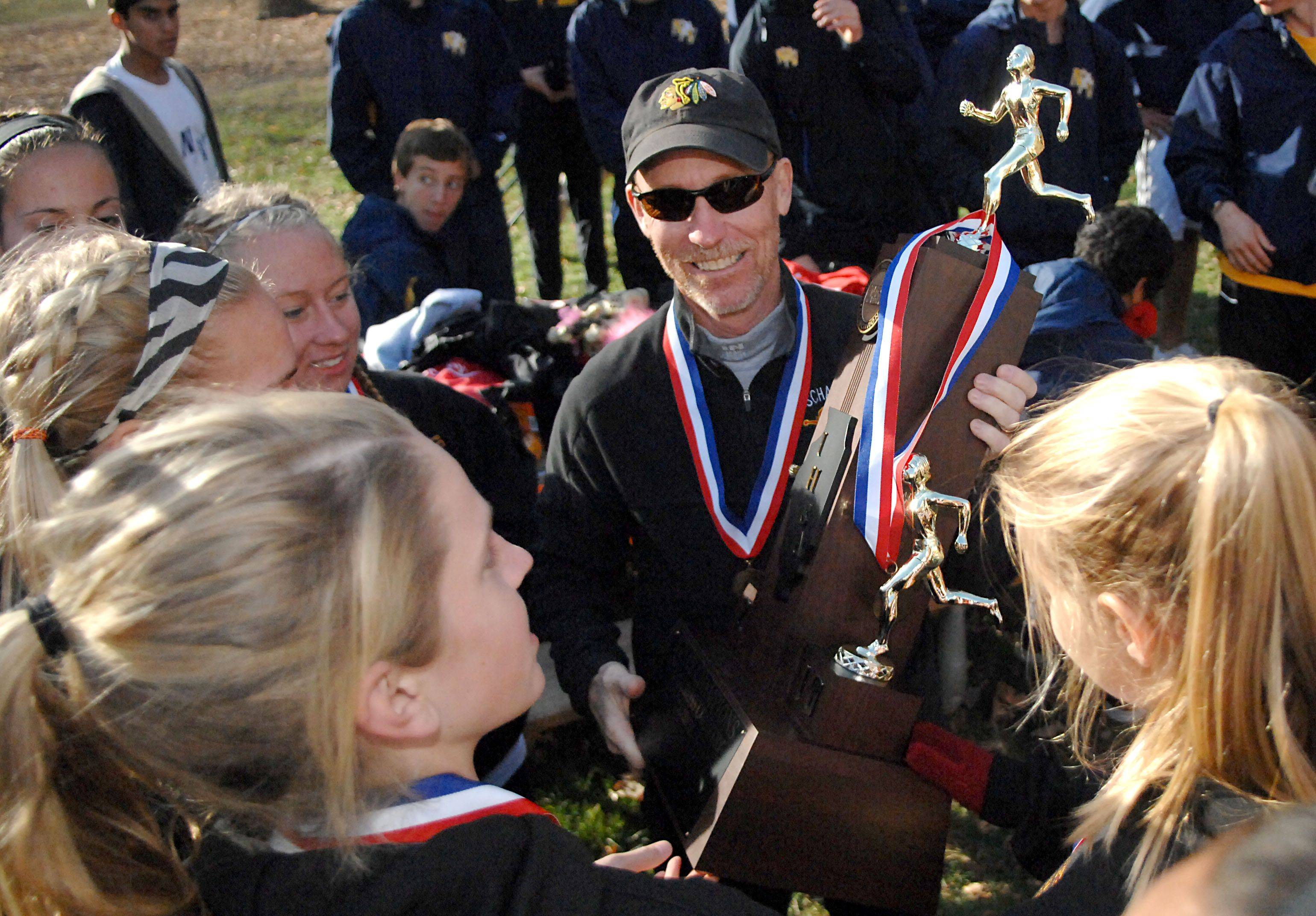 Schaumburg head coach Jon Macnider smiles wide as the girls hand him their first place 3A cross country state trophy after the awards assembly at Detweliler Park in Peoria on Saturday, November 6.