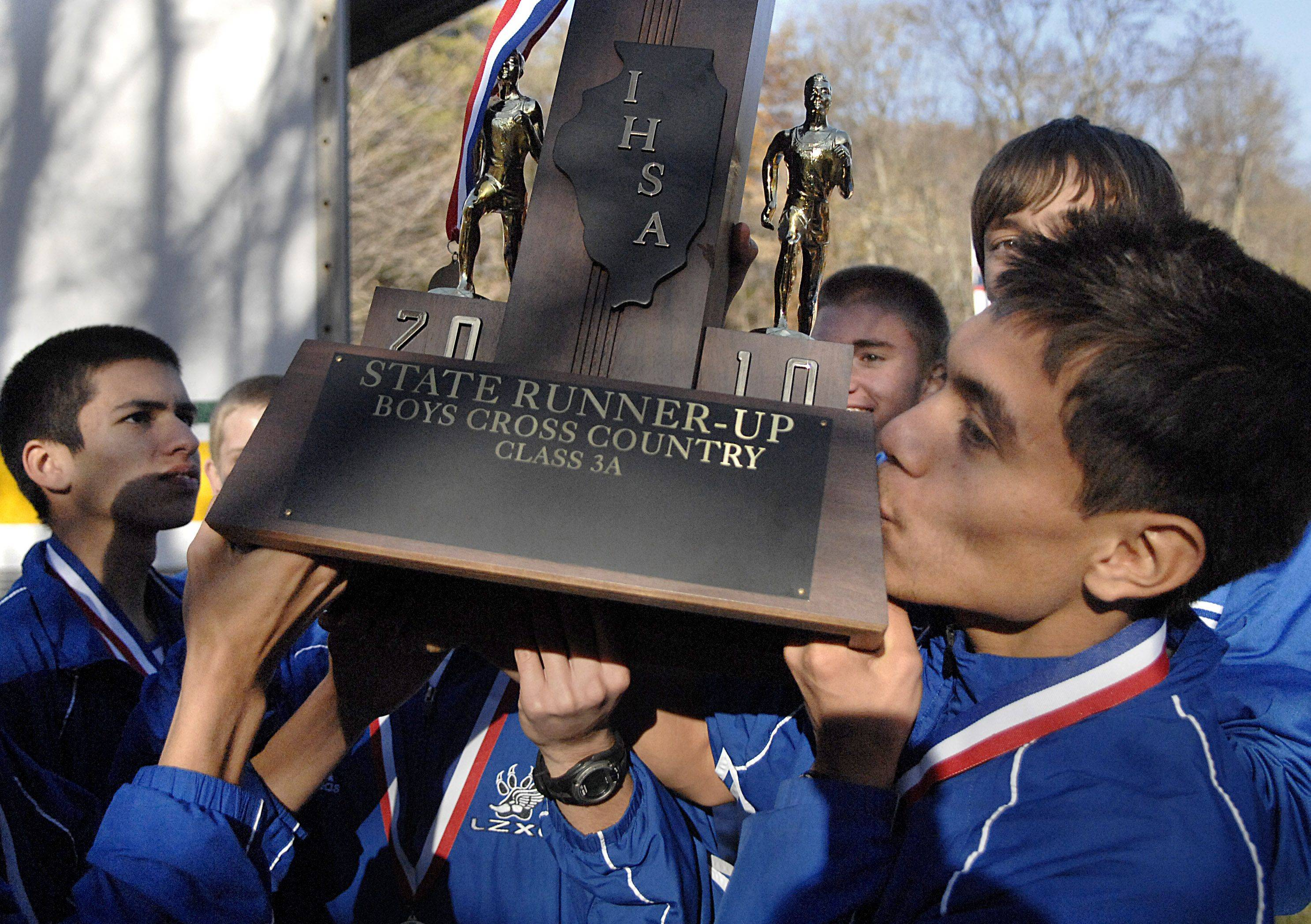 Lake Zurich's Jonathan Ramirez smooches the team's 3A second place trophy for the cross country state meet at Detweiller Park in Peoria on Saturday, November 6.