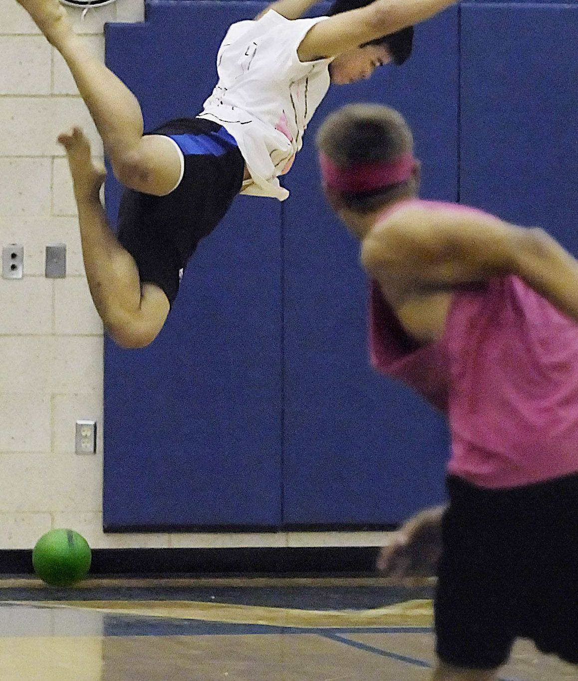 Andy Phorasavong, a senior at Geneva High School, avoids being hit by leaping high above a throw during the championship match of a recent dodgeball tournament to benefit the American Cancer Society. His team won the tournament, which raised $900 in honor of two teachers currently battling breast cancer.