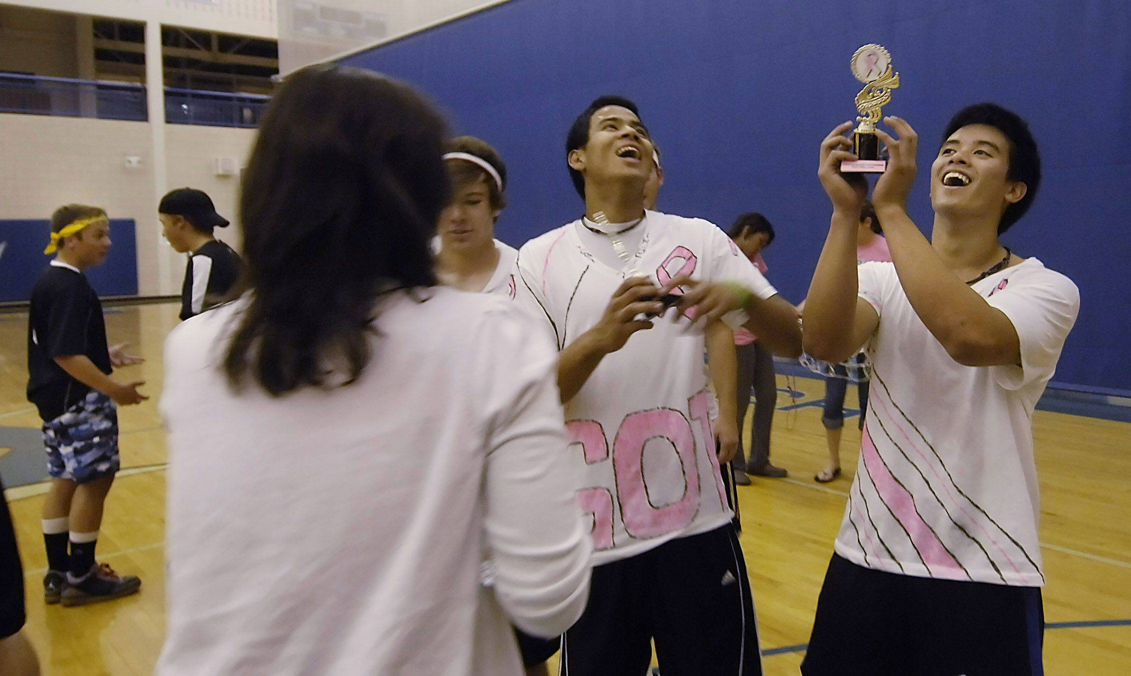 Dennis Leonardo and Andy Phorasavong, of Team Sausage Fest, rejoice in winning the charity dodgeball tournament as opponent Mike Henriksen and a teammate of Team Drogball talk in the background.