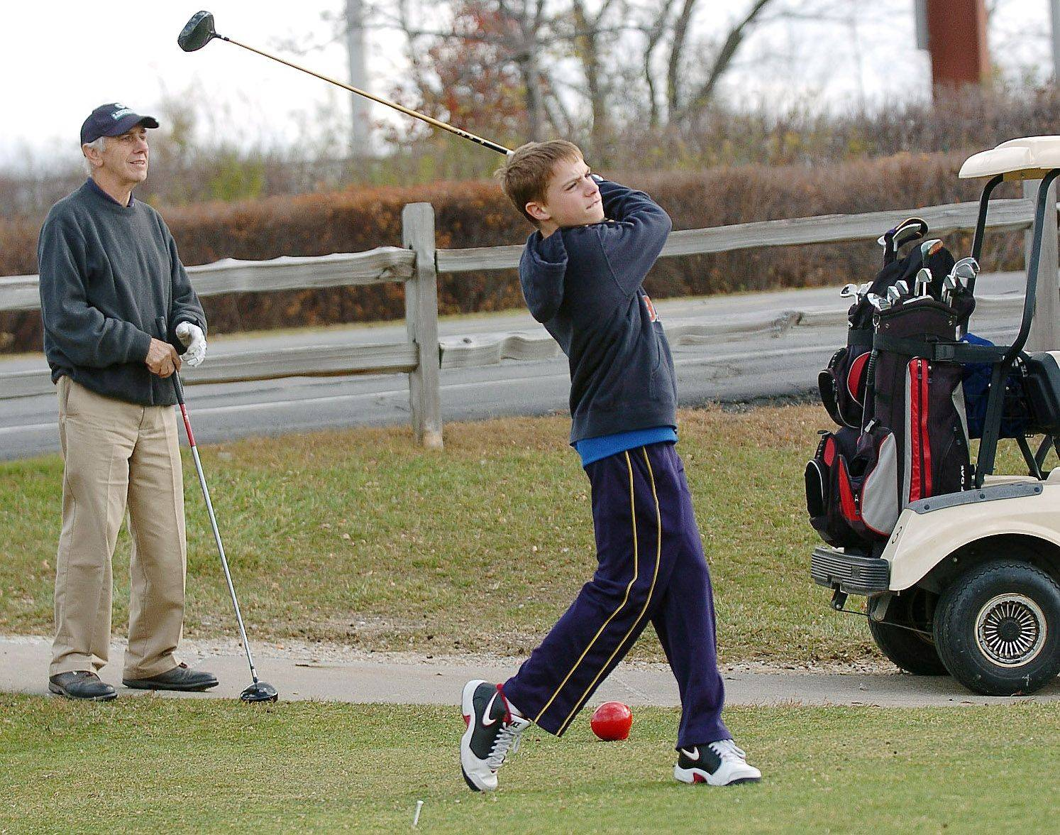 Jim Nix of Palatine watches his grandson Ryan Hodes tee off while playing a round of golf at Twin Lakes Golf and Recreation Area in Palatine.