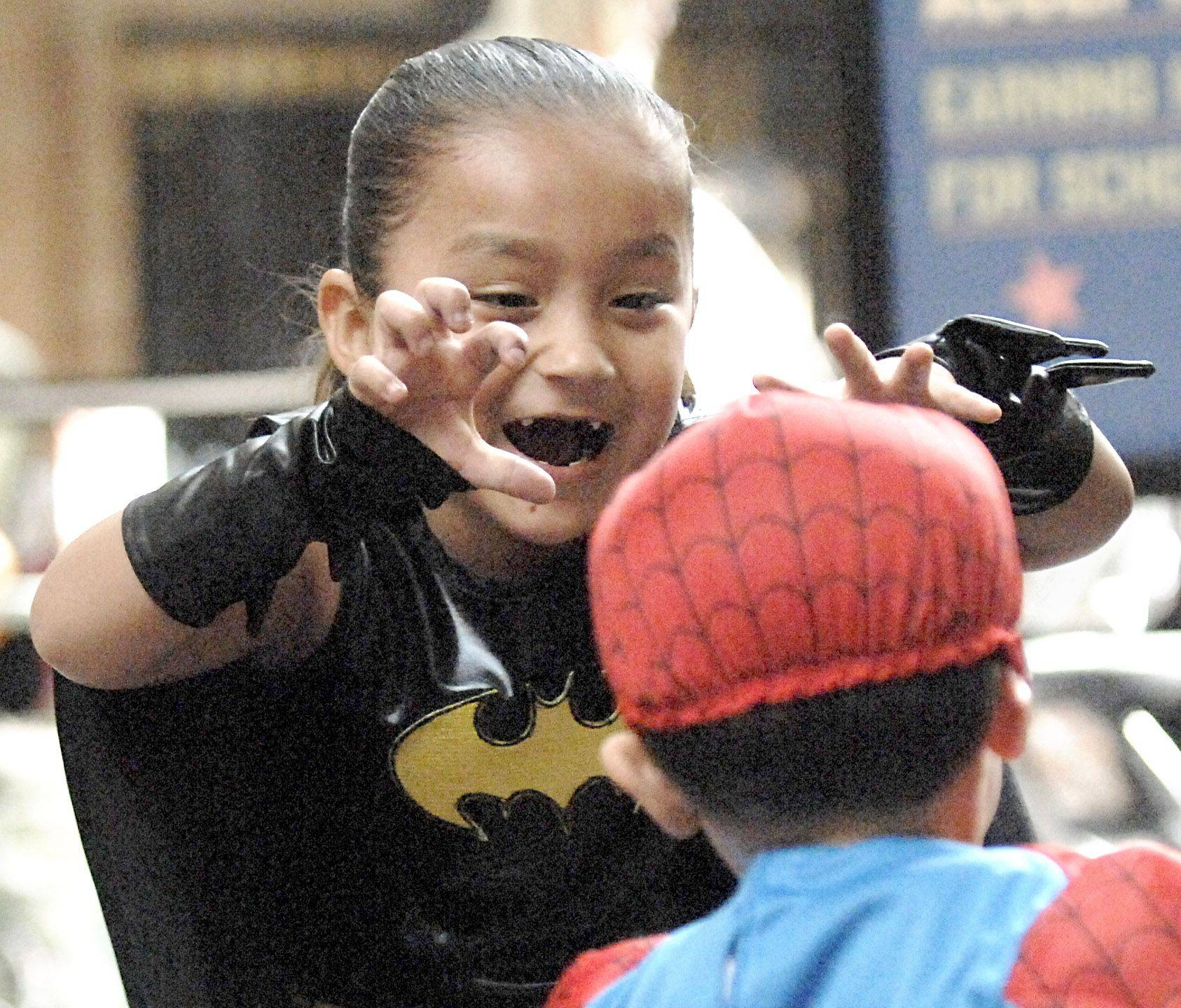 Hailey Hernandez, 4, attempts to spook her cousin David Garcia, 2, while waiting for the costume contest at Spring Hill Mall's Fall Family Festival in West Dundee Saturday. Close to 200 children showed to enter the costume contest. There were 5 top prizes for the best costumes in the categories of funniest, cutest, most creative, look-alike and scariest.