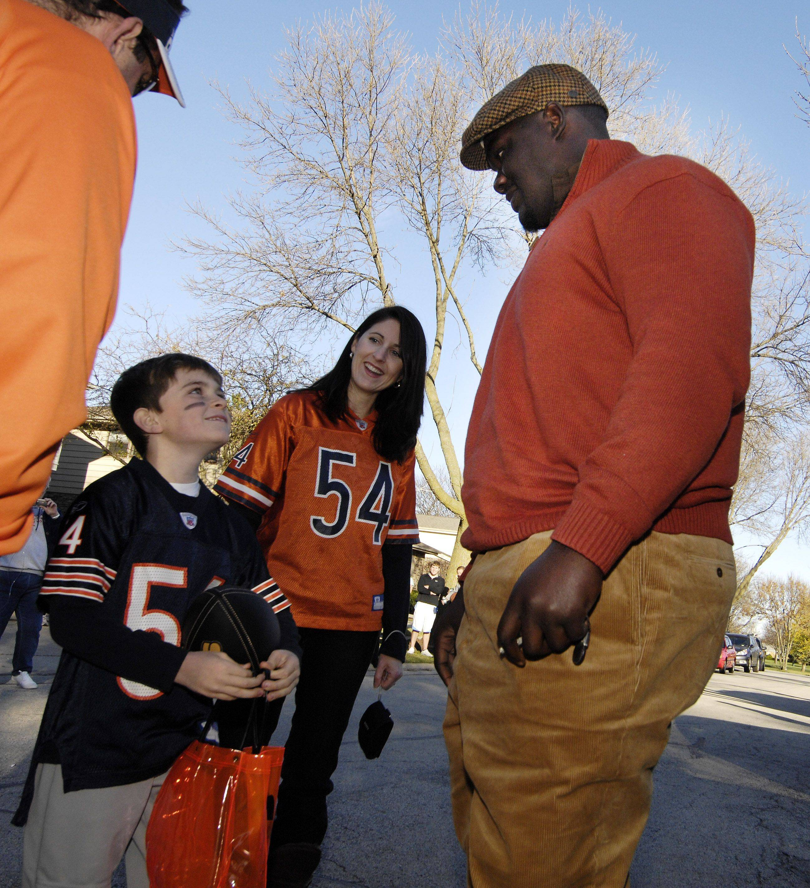 Nine-year-old Ryan Politzki of Arlington Heights and his mom Stacey meet Chicago Bear Tommie Harris for some trick-or-treating. Ryan won a contest sponsored by Goodwill to go trick-or-treating with the football star.