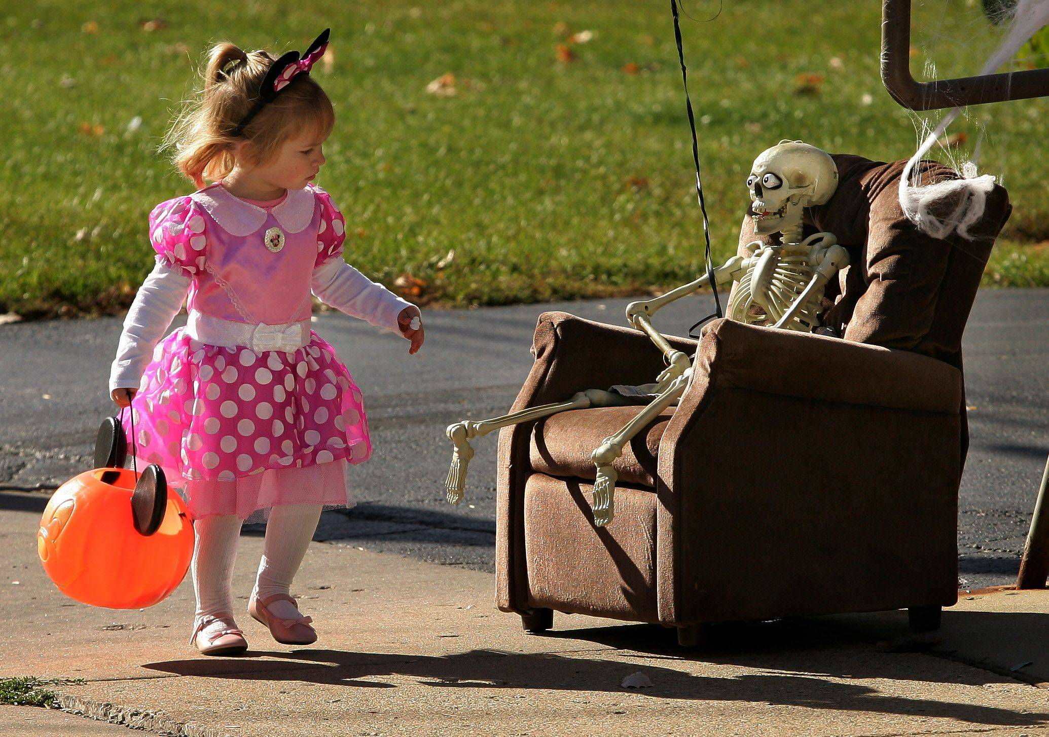 Addison Becker, 2, of Antioch looks at a skeleton sitting in a lounge chair outside Laura's Flower Shoppe during the Lake Villa Halloween Celebration Sunday in the downtown area.