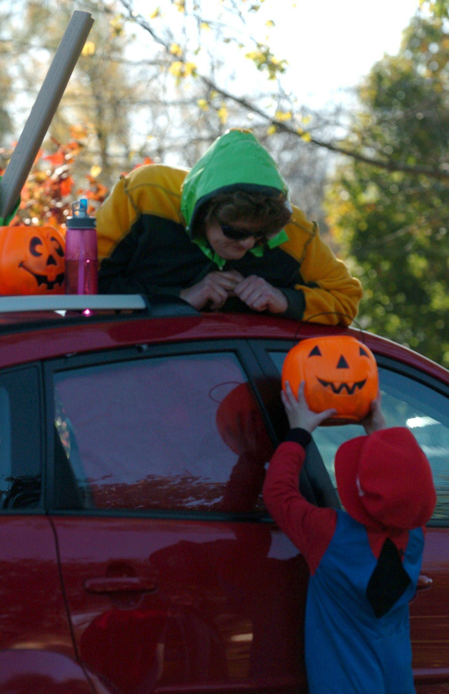 Paster Jan Comerford of Community United Methodist Church in South Elgin hands out candy dressed as a worm in her 'Pontiac apple' to 5-year-old Donald Lux during the Trunk-or-Treat event Sunday.