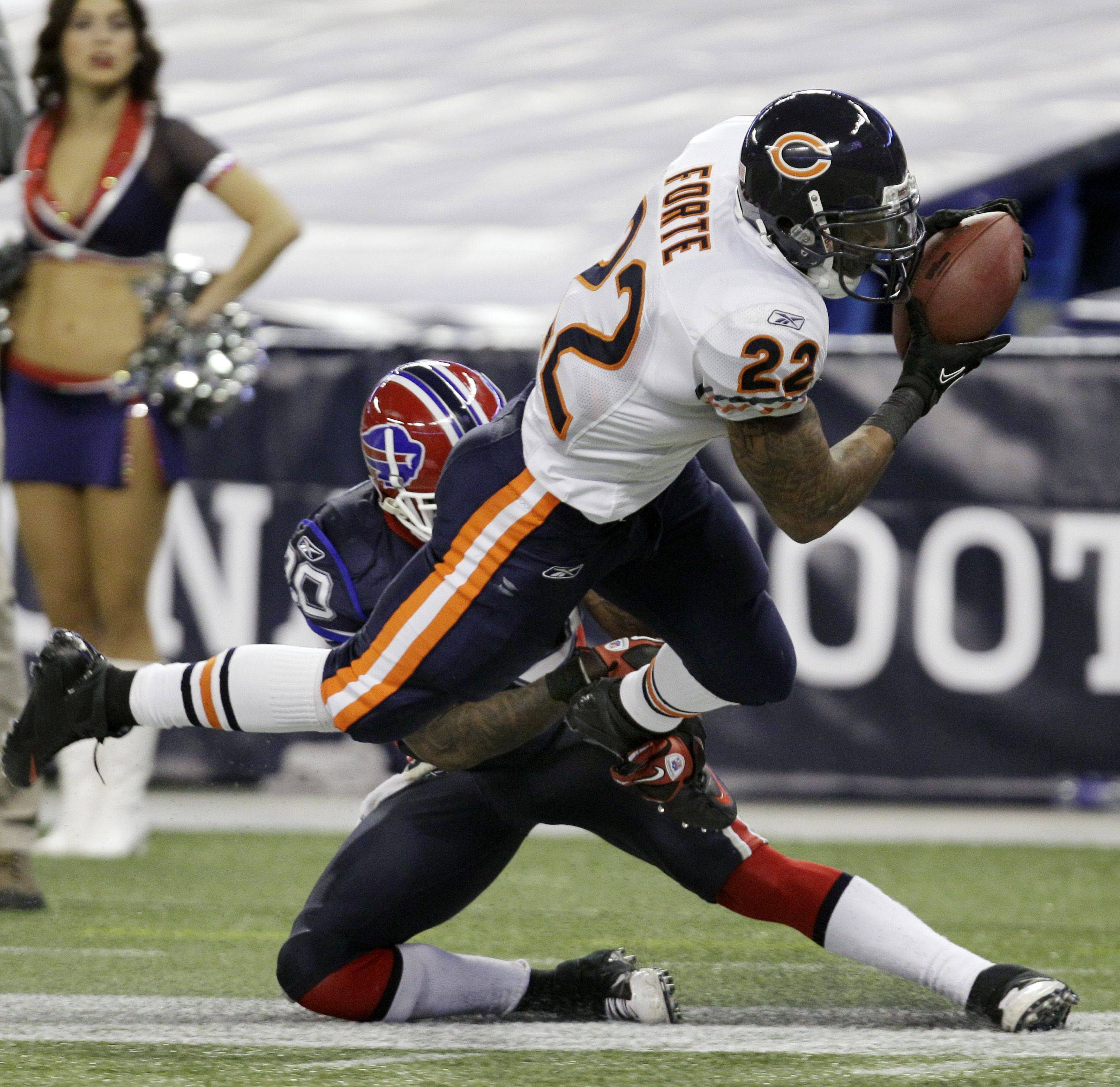 Chicago Bears' Matt Forte runs under pressure from Buffalo Bills' Donte Whitner during the second half of an NFL football game.